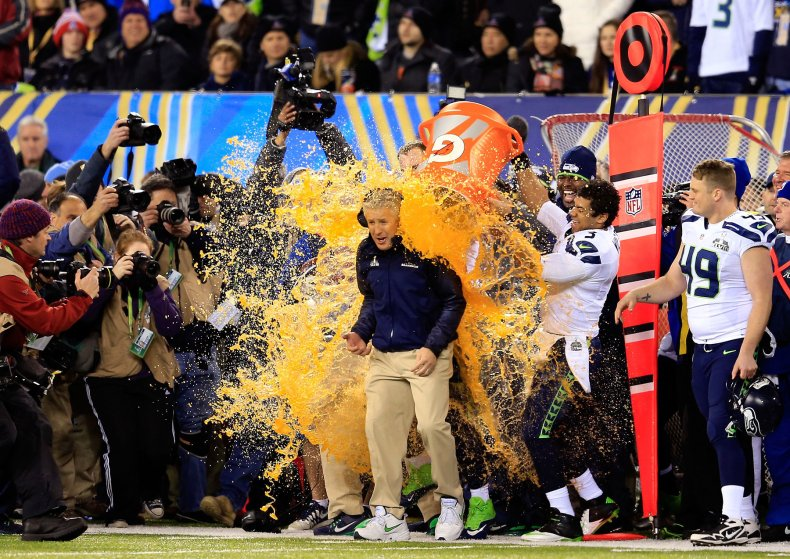 Tight end Zach Miller and quarterback Russell Wilson of the Seattle Seahawks dump Gatorade on head coach Pete Carroll in the fourth quarter of Super Bowl XLVIII.