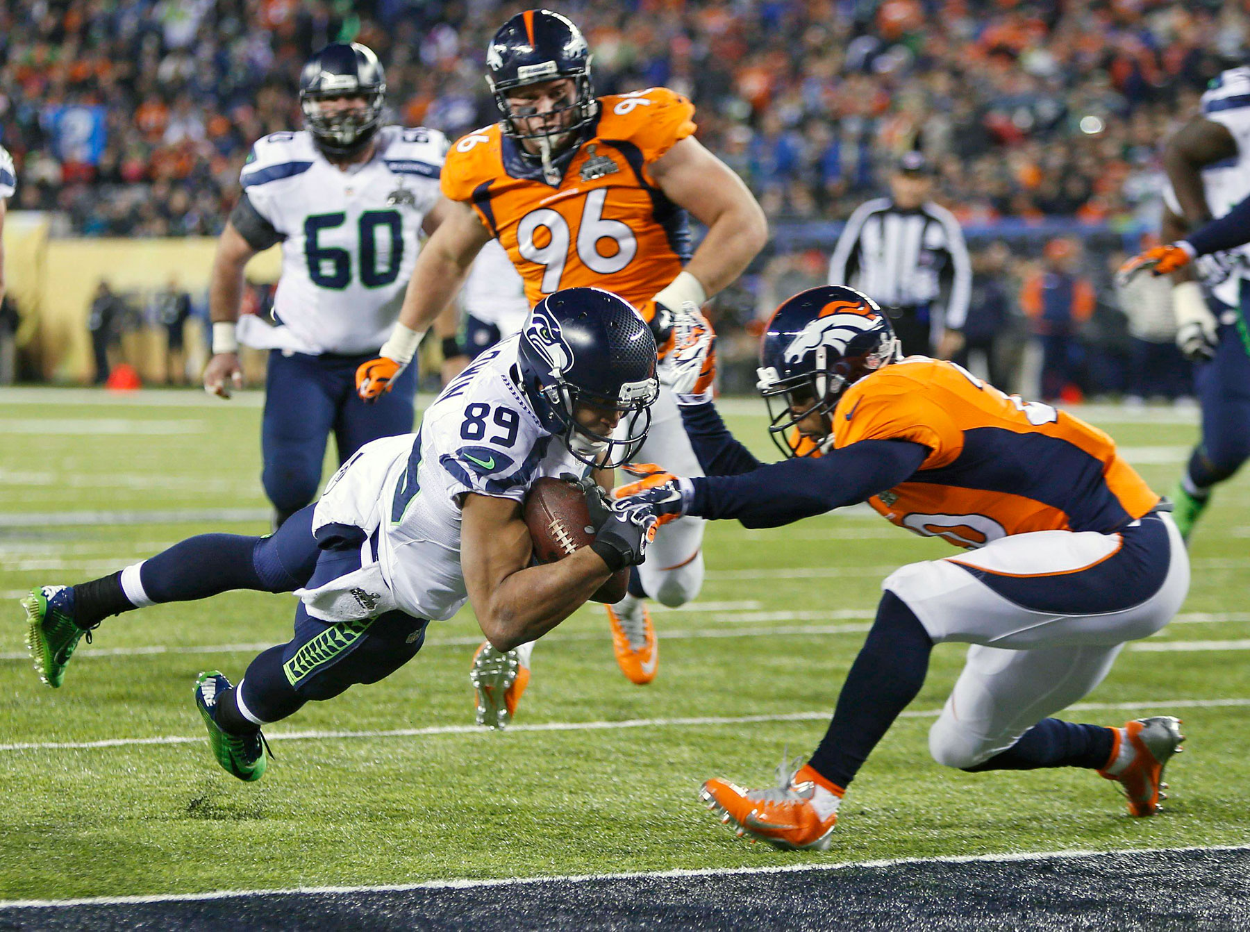 Seattle Seahawks wide receiver Doug Baldwin dives into the end zone for a touchdown past Denver Broncos free safety Mike Adams during the fourth quarter.