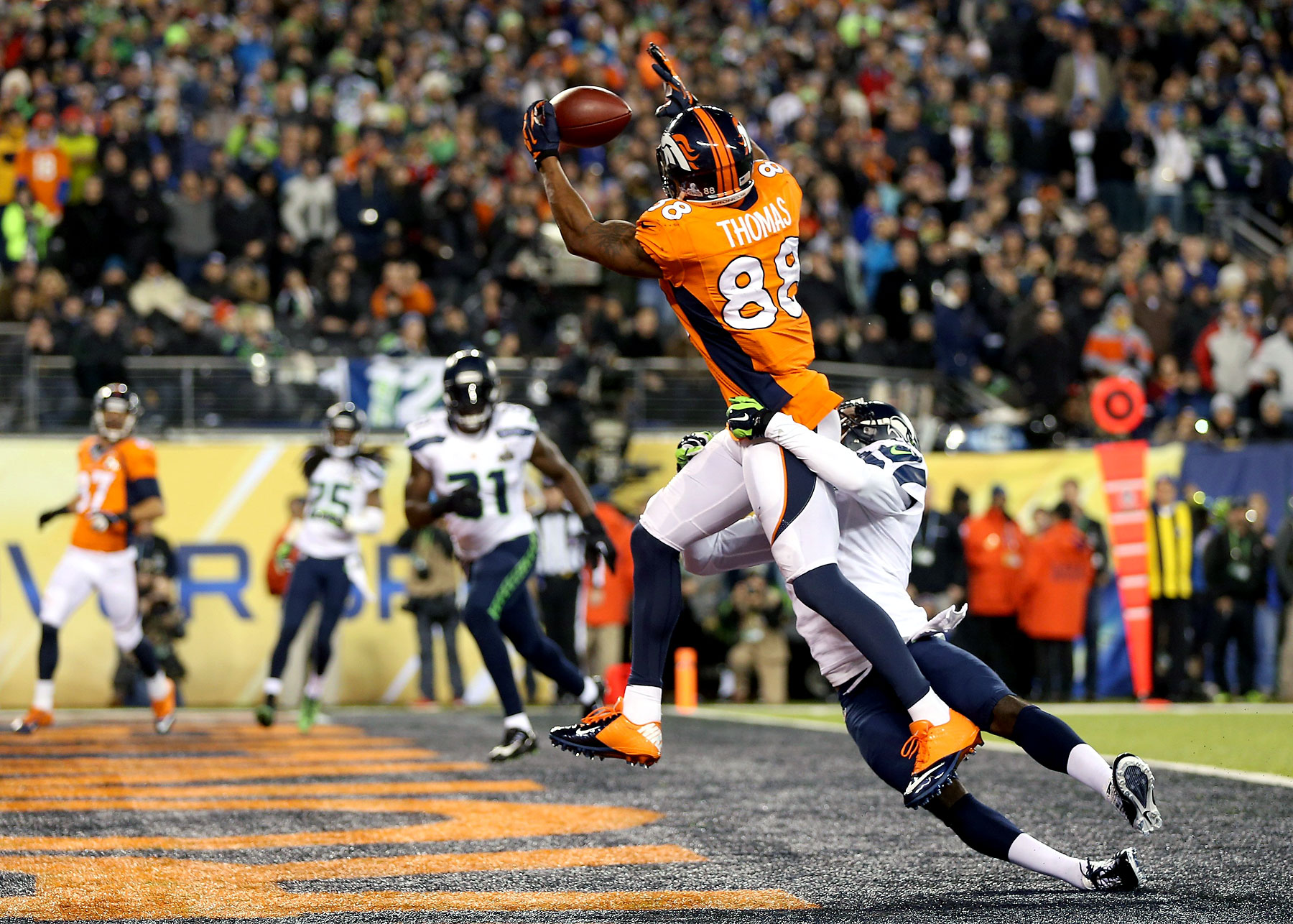 Wide receiver Demaryius Thomas of the Denver Broncos ran 14 yards to score a touchdown in the third quarter against cornerback Byron Maxwel of the Seattle Seahawks.