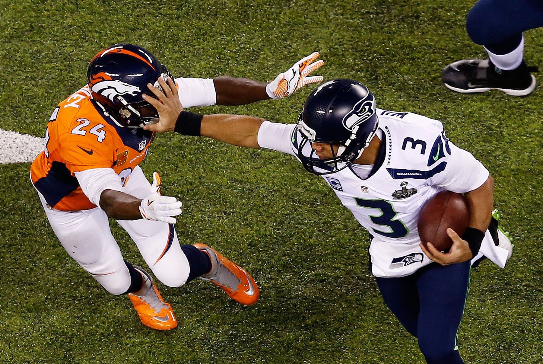Quarterback Russell Wilson of the Seattle Seahawks stiff arms cornerback Champ Bailey of the Denver Broncos.
