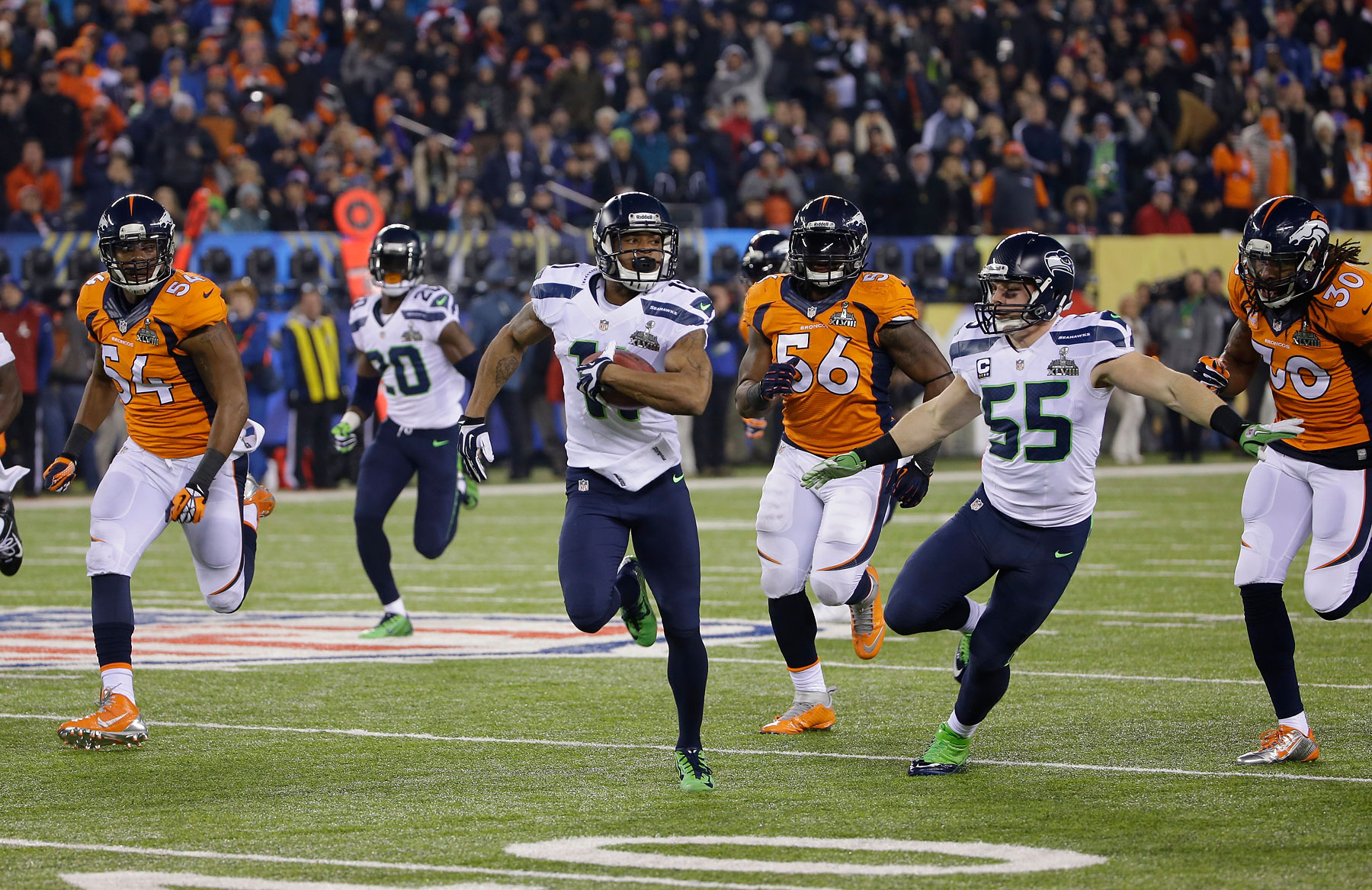Seattle Seahawks' Percy Harvin, center, returns a kickoff 87-yards for a touchdown during the opening seconds of the third quarter.