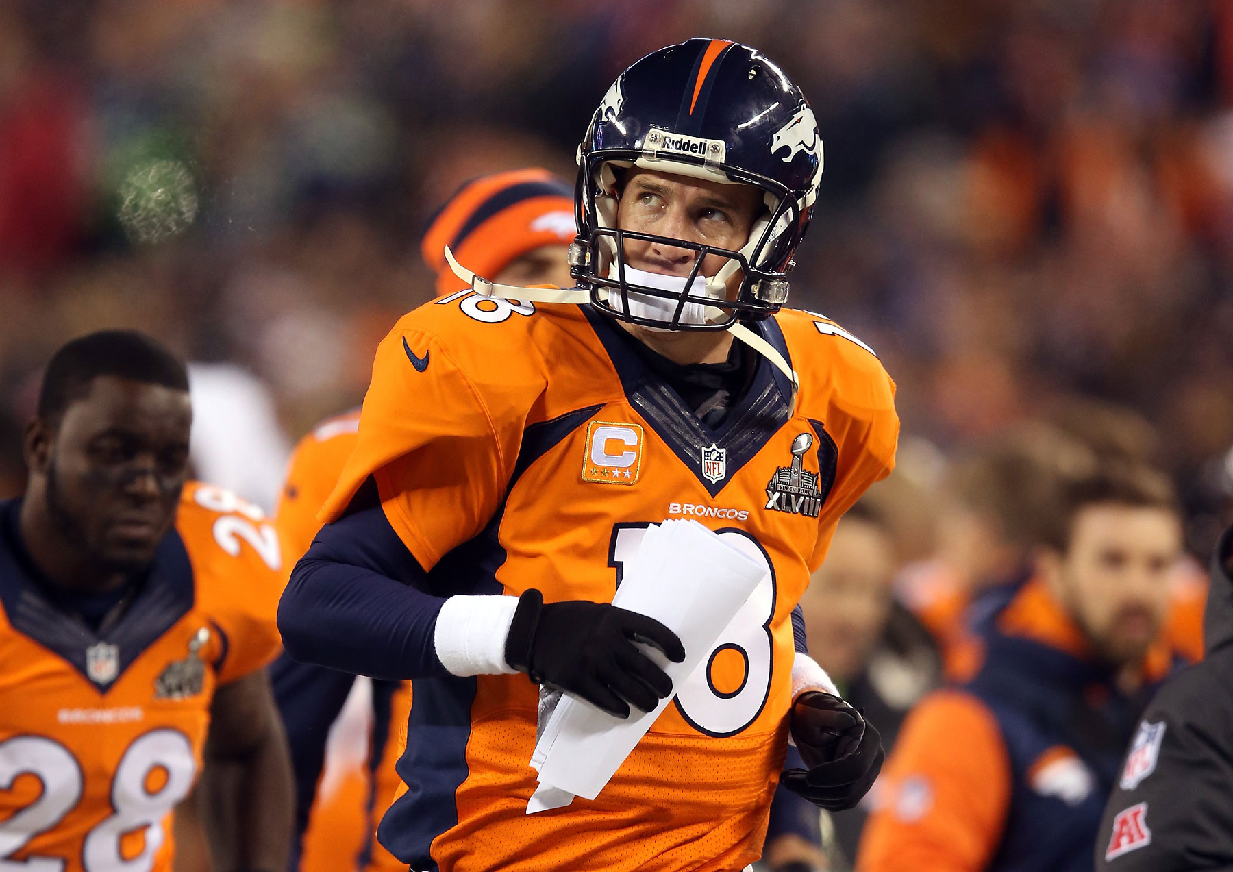 Quarterback Peyton Manning of the Denver Broncos runs off the field at the end of the first half.