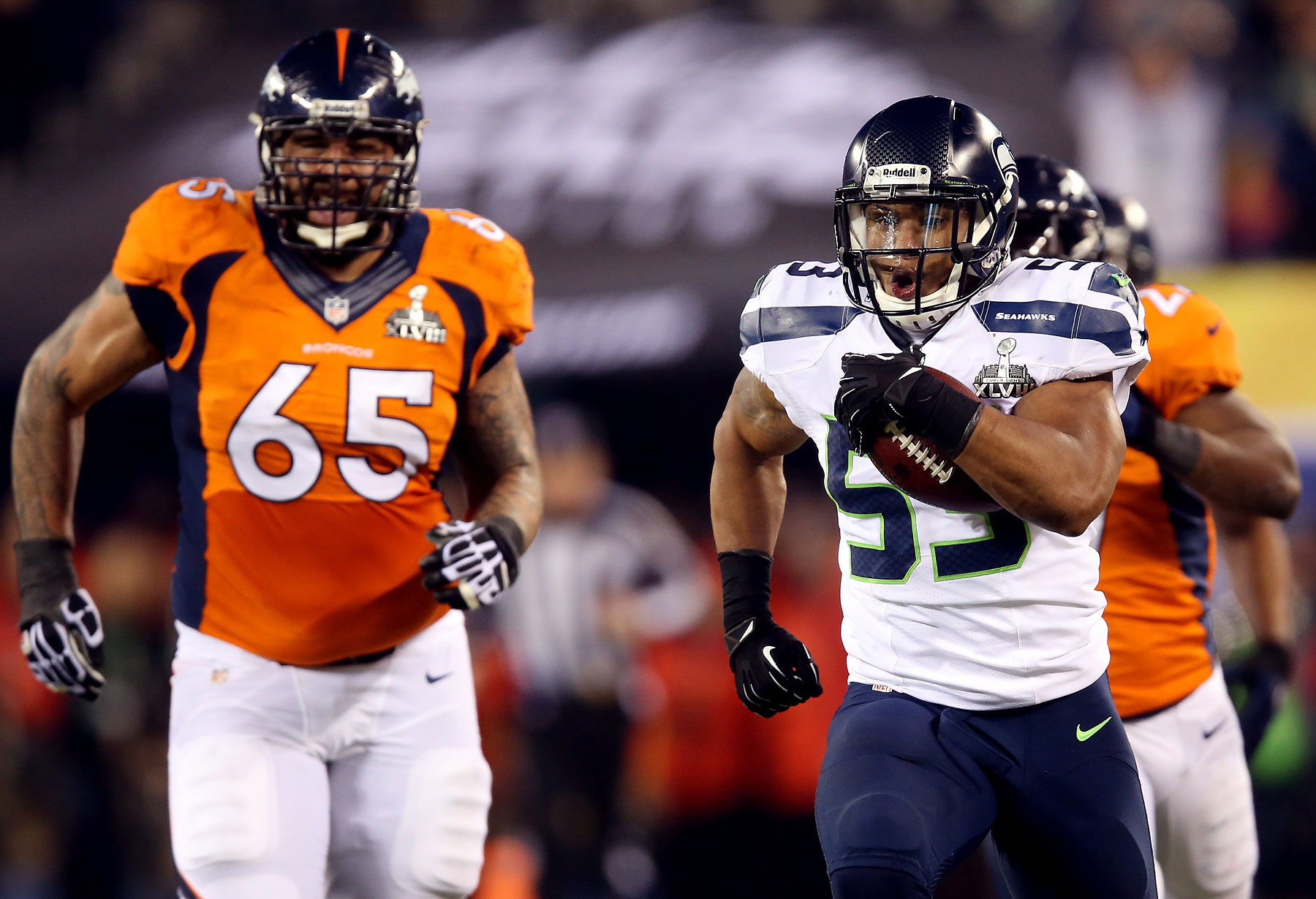 Outside linebacker Malcolm Smith of the Seattle Seahawks runs 69-yards for a touchdown against guard Louis Vasquez of the Denver Broncos after intercepting a pass intended for running back Knowshon Moreno of the Denver Broncos in the second quarter.