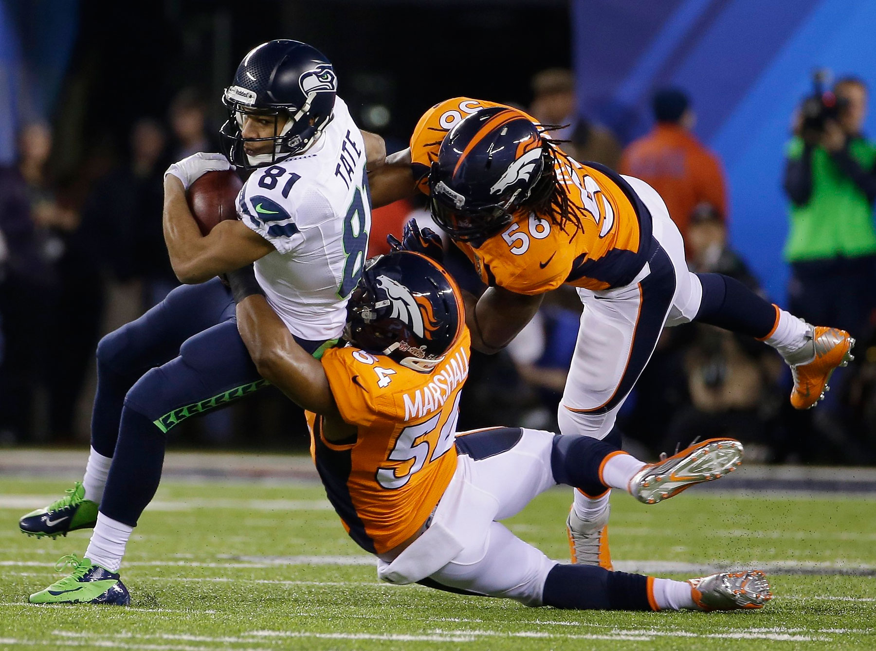 Seattle Seahawks' Golden Tate is tackled by Denver Broncos' Brandon Marshall and Nate Irving during the first quarter.