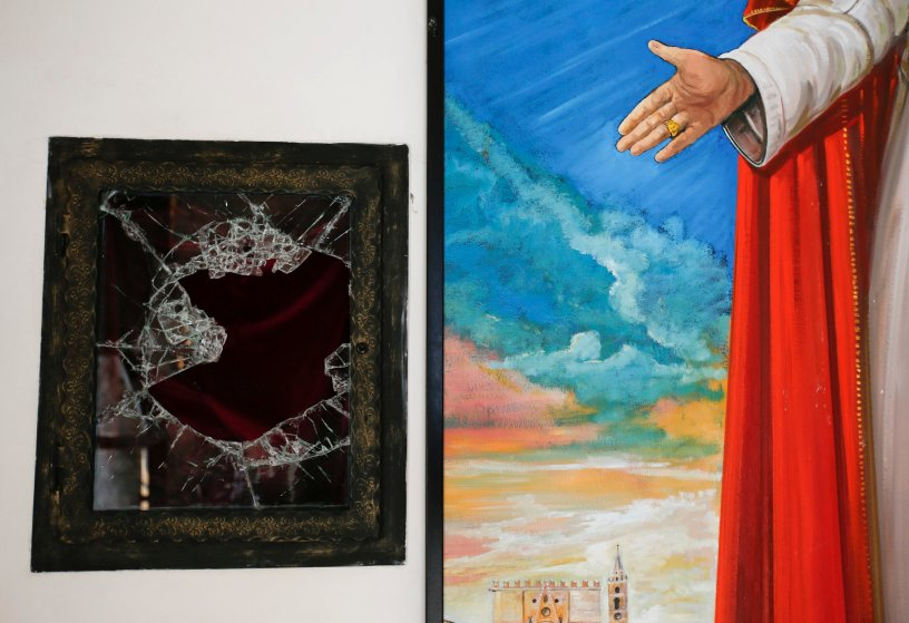 A broken glass of a niche where the reliquary with the blood of the late Pope John Paul II was located is seen next to a painting of the late Pope in the small mountain church of San Pietro della Ienca, near the city of L'Aquila Jan. 28, 2014 .Thieves broke into a small church in the mountains east of Rome and stole the reliquary with the blood of the late Pope John Paul II, a custodian said.