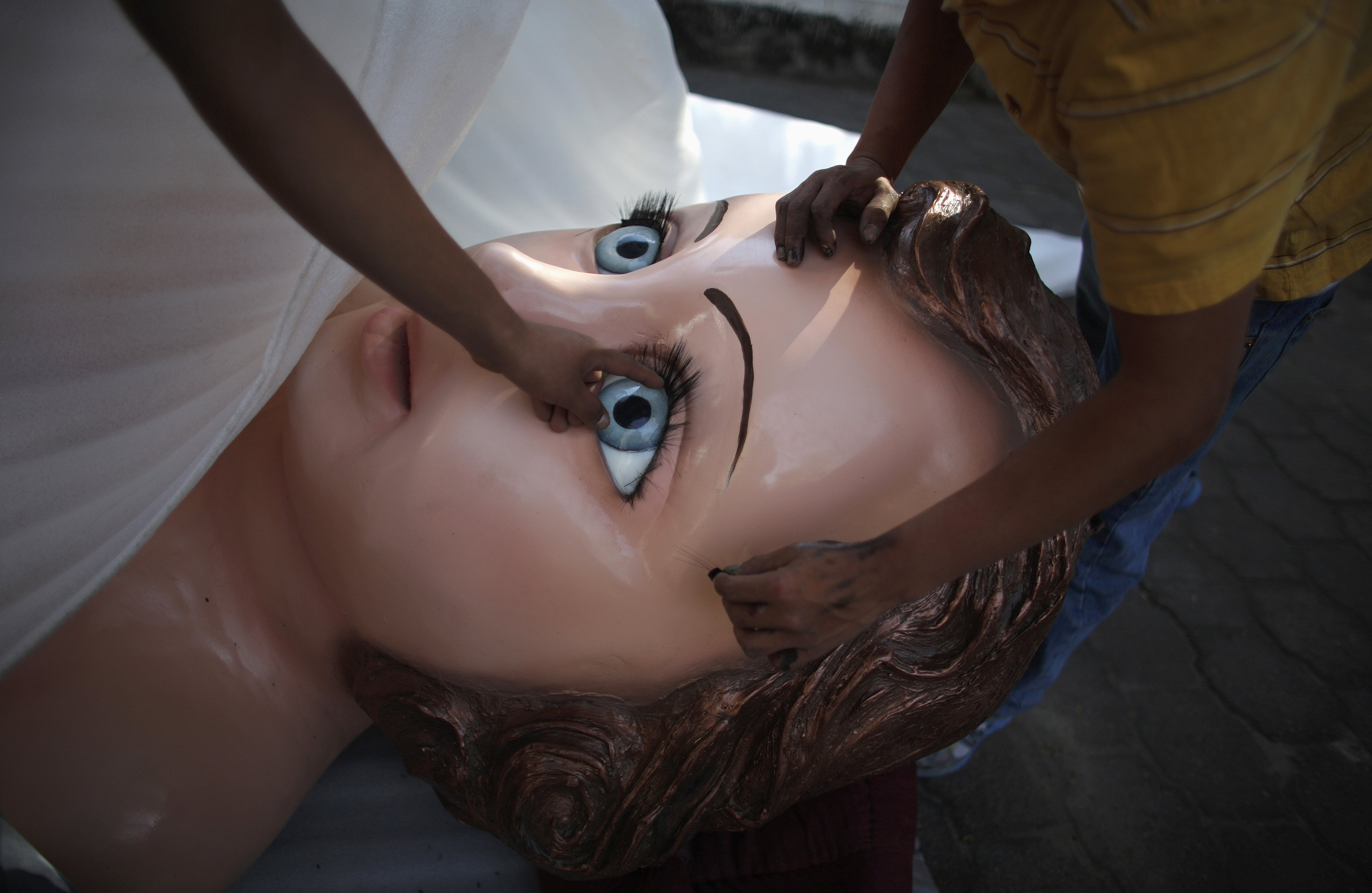 Members of the Morphix Group inspect the eyelashes of a baby Jesus statue to be displayed during the annual Candlemas celebrations at the Sanctuary of the Lord of the Holy Sepulchre in the Iztapalapa borough of Mexico City February 1, 2014.