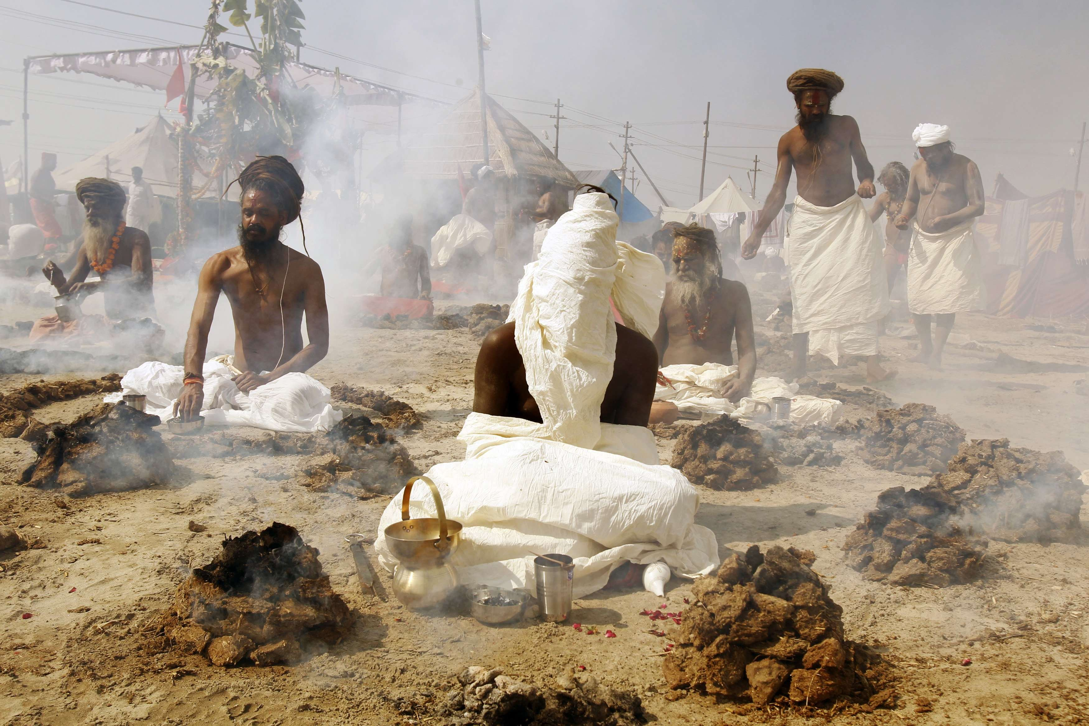 Sadhus, or Hindu holy men, perform prayers while sitting inside circles of burning  Upale  (or dried cow dung cakes) on the banks of the river Ganges during the Magh Mela festival in the northern Indian city of Allahabad Feb. 4, 2014.