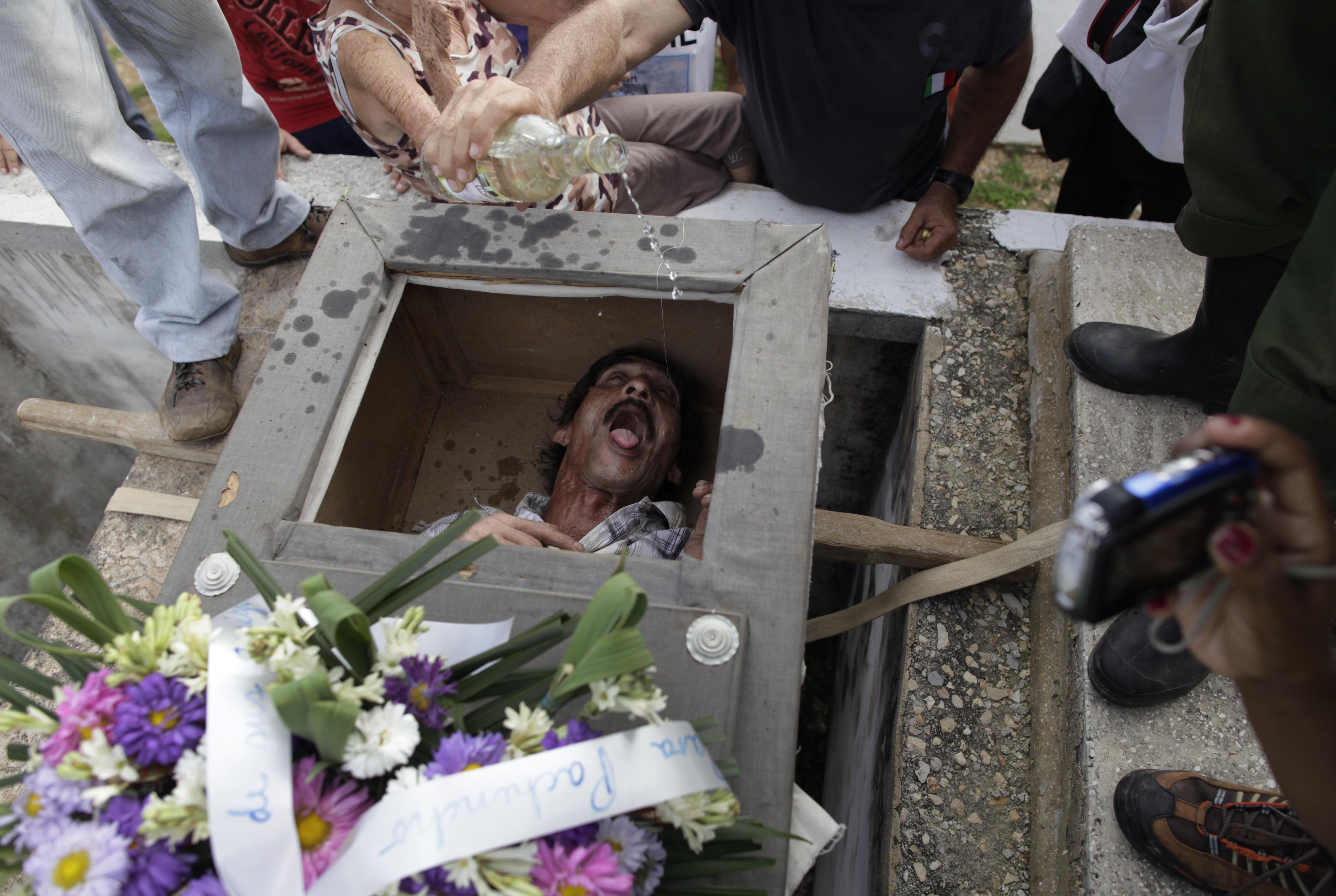 Divaldo Aguiar, who plays the part of Pachencho, lies inside a mock coffin as villagers splash rum into Aguiar's mouth during the Burial of Pachencho celebration at a cemetery in Santiago de Las Vegas, Cuba, Feb. 5.