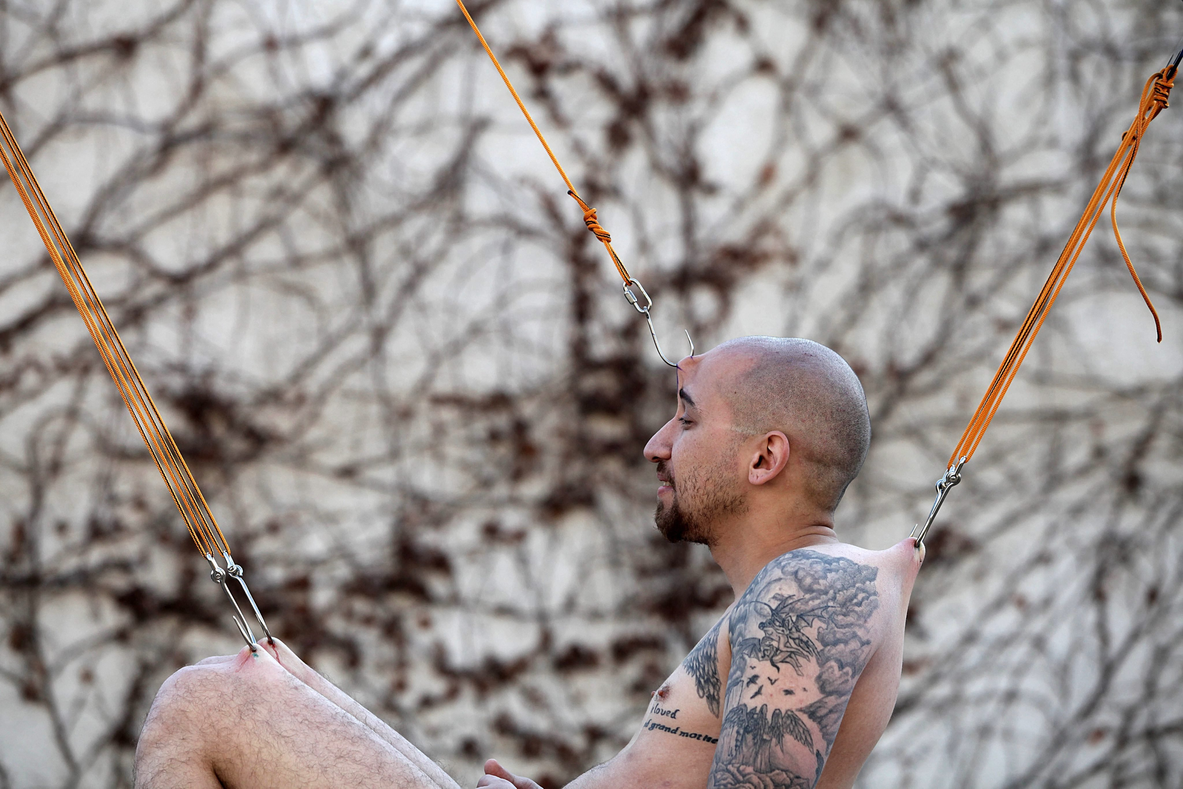 An Israeli hanging on hooks performs the Suspension (body modification) during the annual Israel Tattoo Convention in Tel Aviv, Israel, Feb. 8, 2014. The event took place for the second time in Israel featuring the best tattoo artists of the country.
