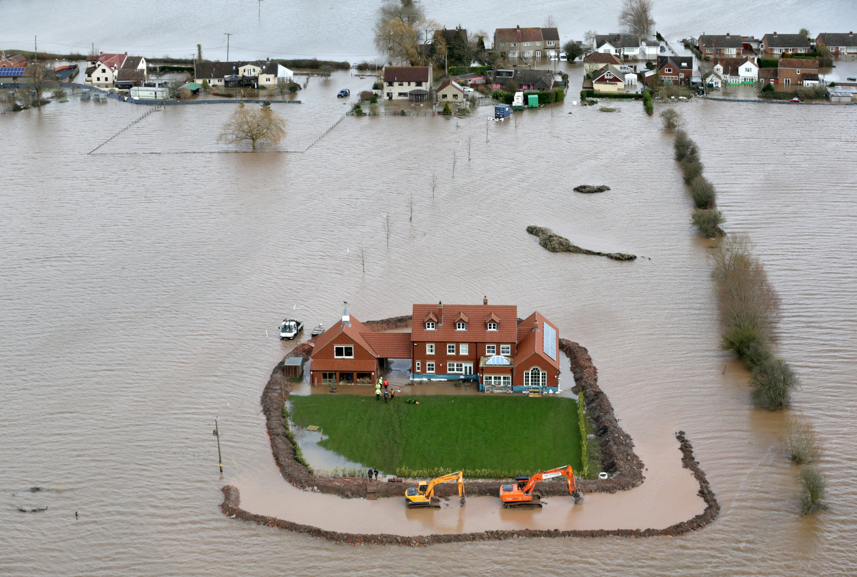Worker's continue to build flood defences around Moorland resident Sam Notaro's house in the flooded village of Moorland near Bridgwater on the Somerset Levels on Feb. 10, 2014 in Somerset, England. Thousands of acres of the Somerset Levels have been under water for weeks, yet flood levels are still rising and worryingly, more rain is forecast for later this week.
