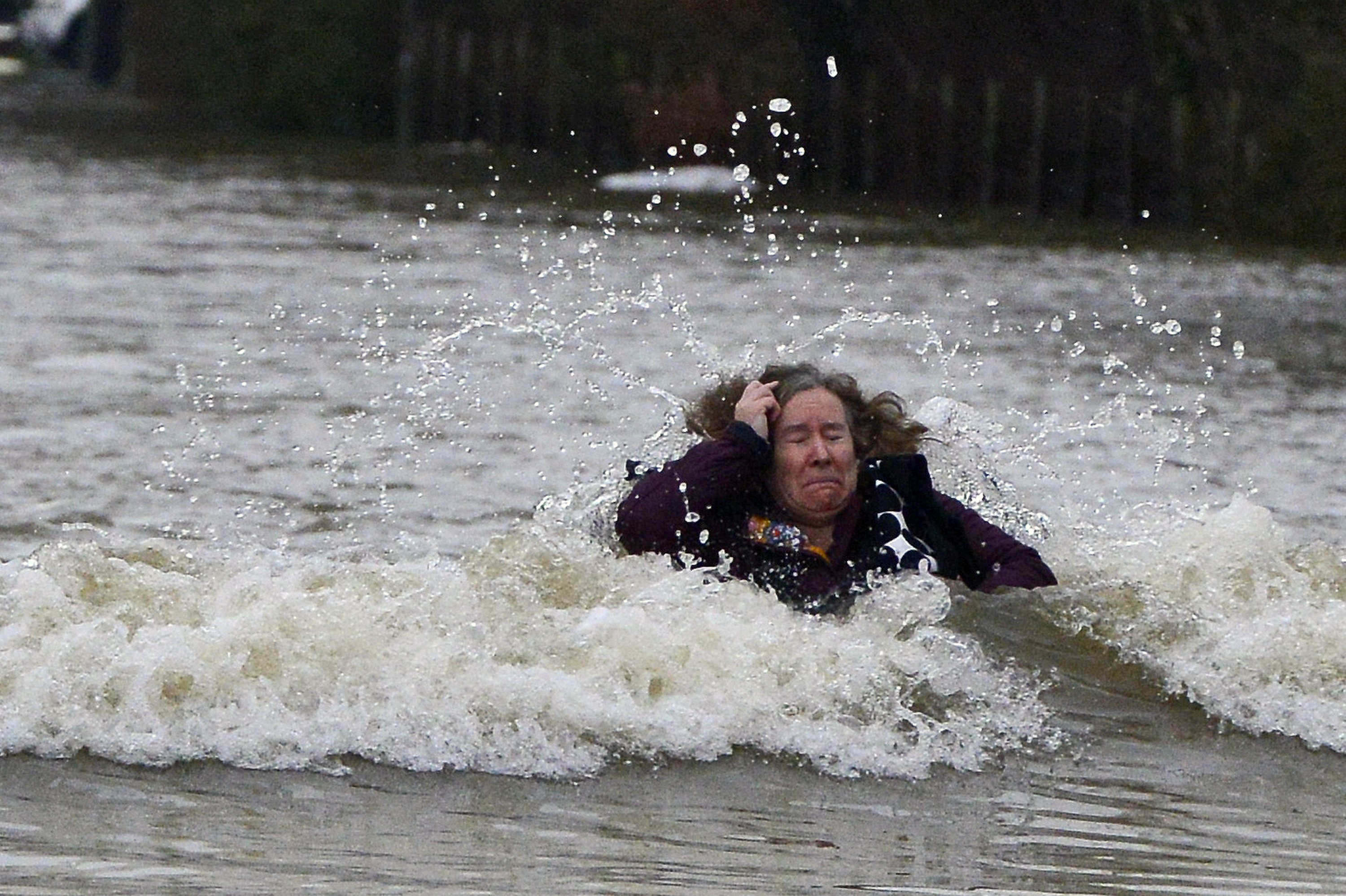 A woman becomes caught up in a lorries wash during flooding, Feb. 10, 2014, in Old Windsor in Berkshire  after the River Thames burst its banks.