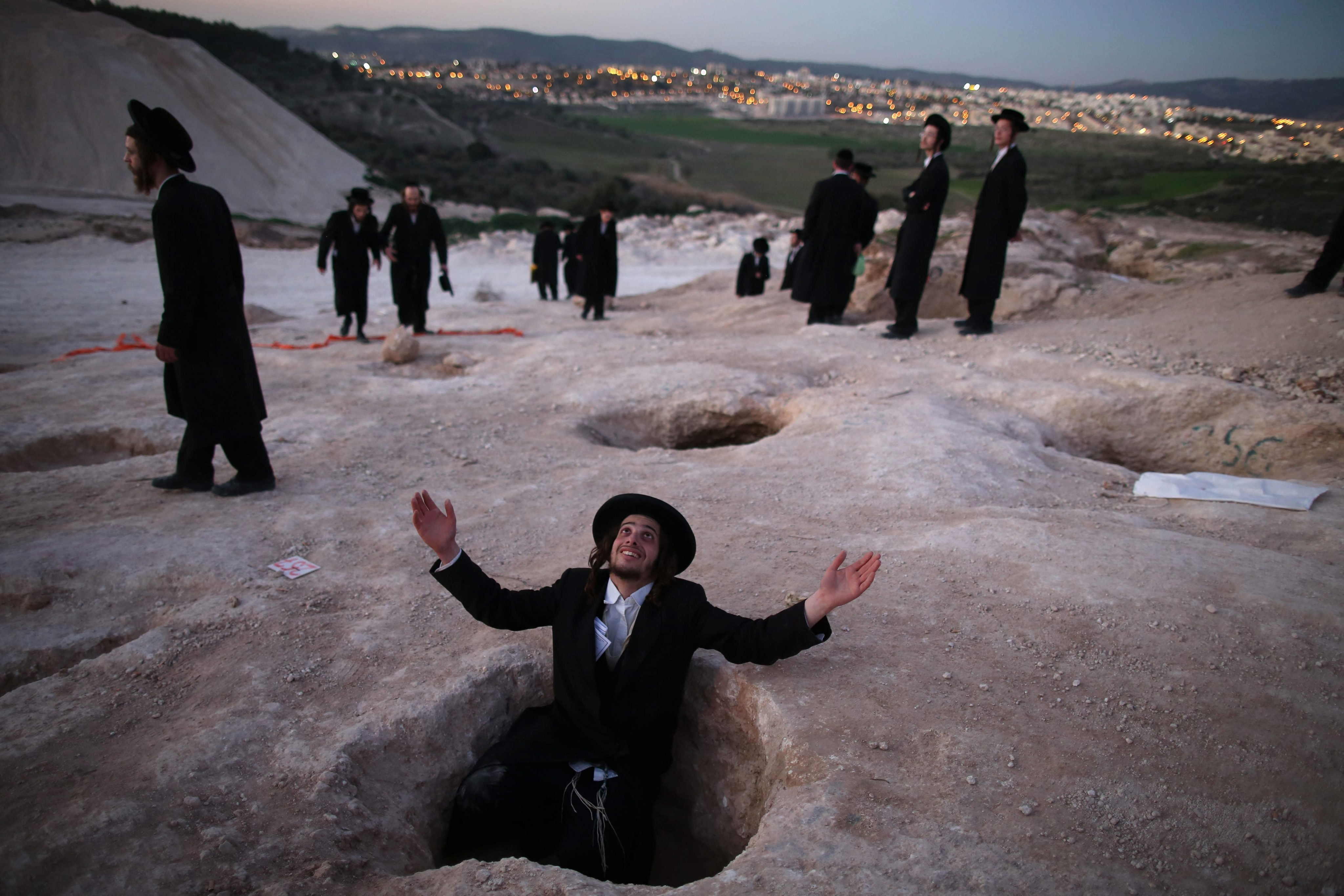 An Ultra-Orthodox Jewish man sits in a hole and prays during a demonstration in Beit Shemesh, Israel, Feb. 12, 2014. Hundreds of Ultra-Orthodox Jews protested against the construction of new housing units, believing they would be built at the site of ancient Jewish graves.