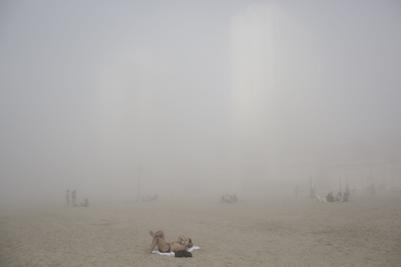 Israelis enjoy the beach under heavy fog at the Mediterranean Sea beach front in Tel Aviv, Feb. 20, 2014.