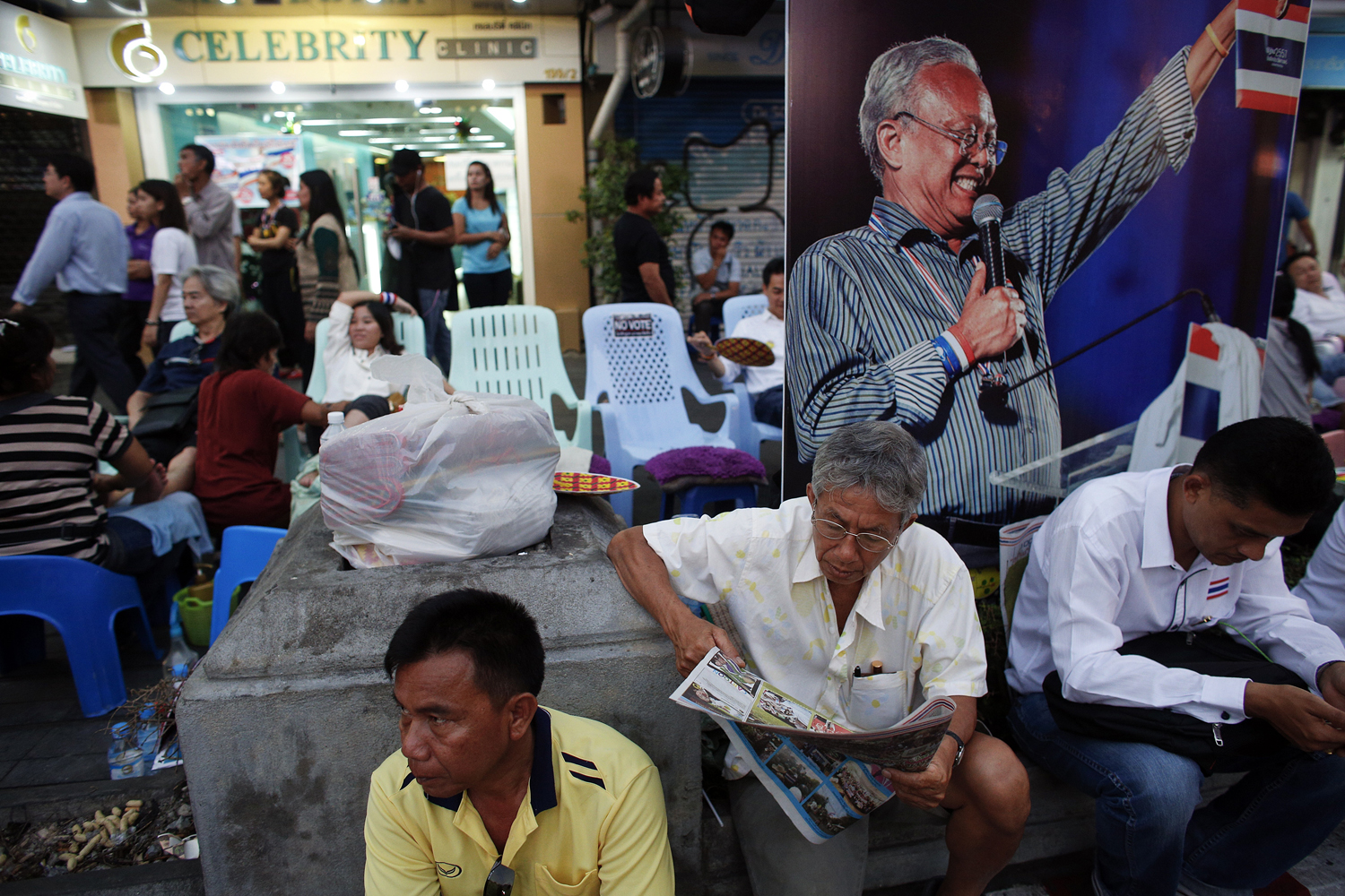 Anti-government protesters enjoy a massage and read papers near a picture of protest leader Suthep Thaugsuban in an occupied area, in downtown Bangkok Feb. 6, 2014