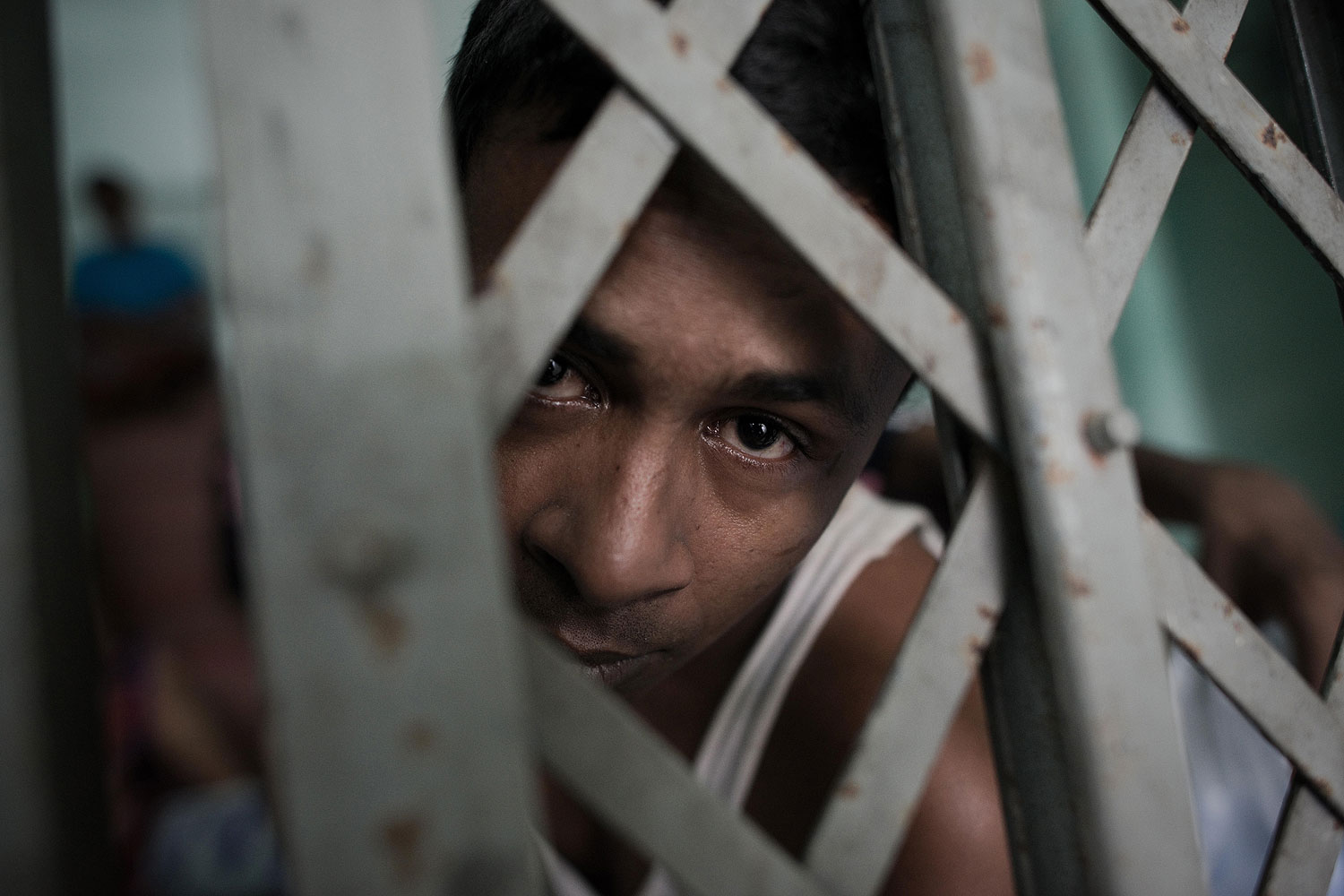 A Muslim Rohingha asylum seeker stands inside a cell at the Thai immigration detention centre in Phangnga, southern Thailand