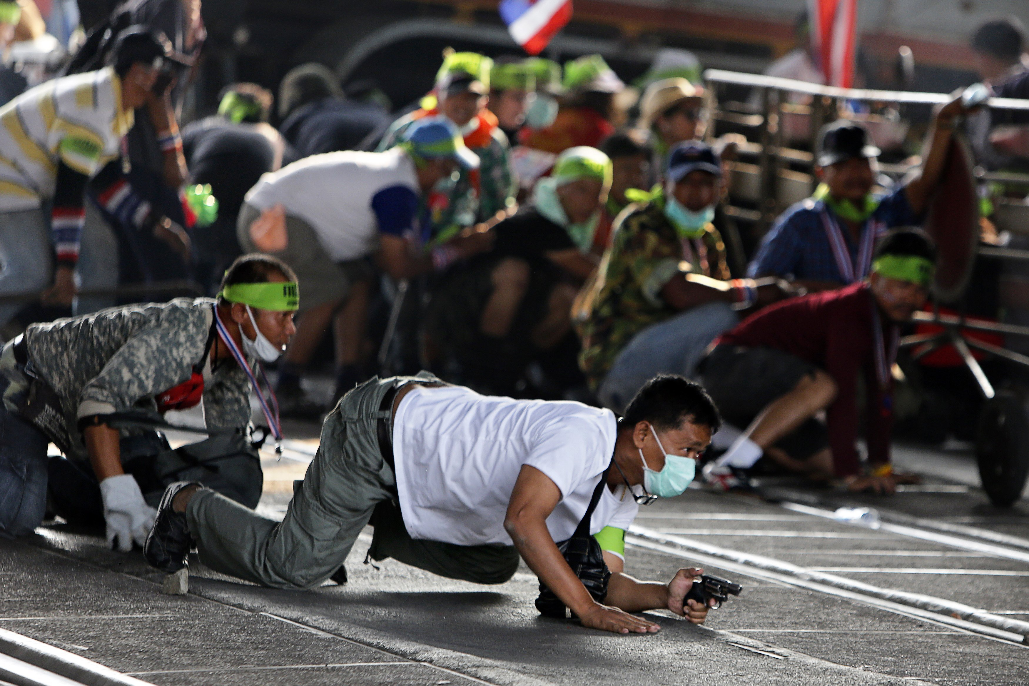 An anti-government protester crawls with his pistol during a gunfight between supporters and opponents of Thailand's government near Laksi district office in Bangkok Feb. 1, 2014.