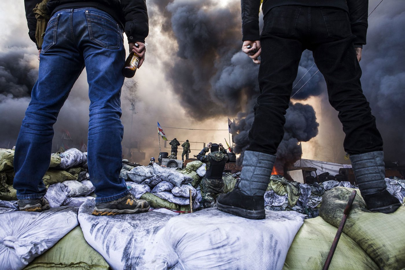 Anti-government demonstrators stand on barricades during clashes with riot police, Feb. 18, 2014.