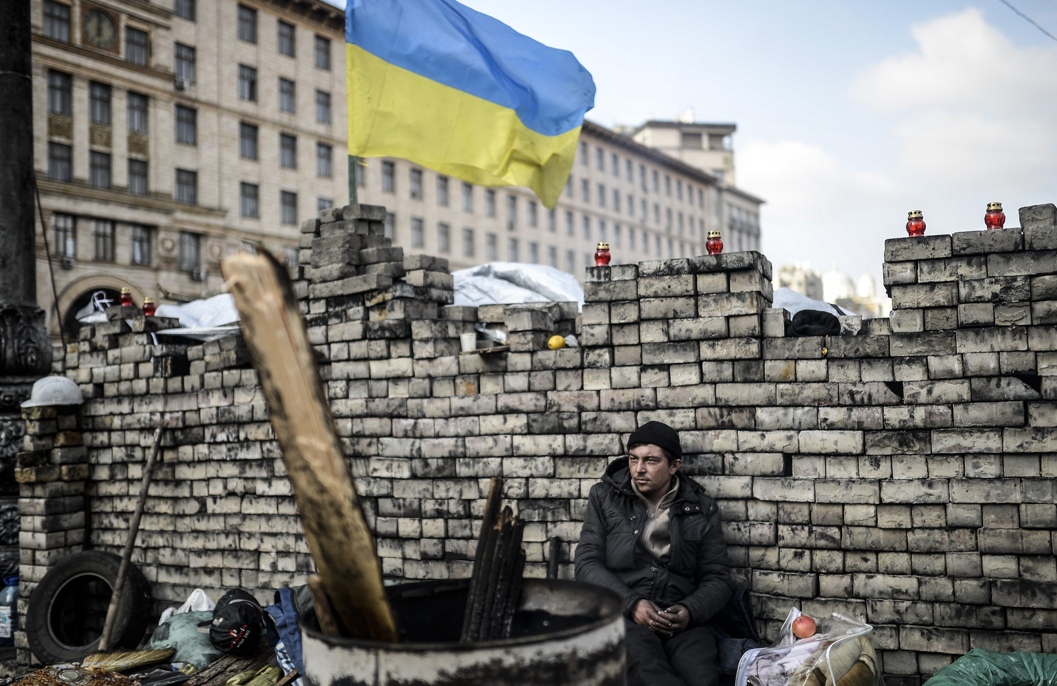 An antigovernment protester sits behind a barricade on Kiev's Independence Square on Feb. 24, 2014