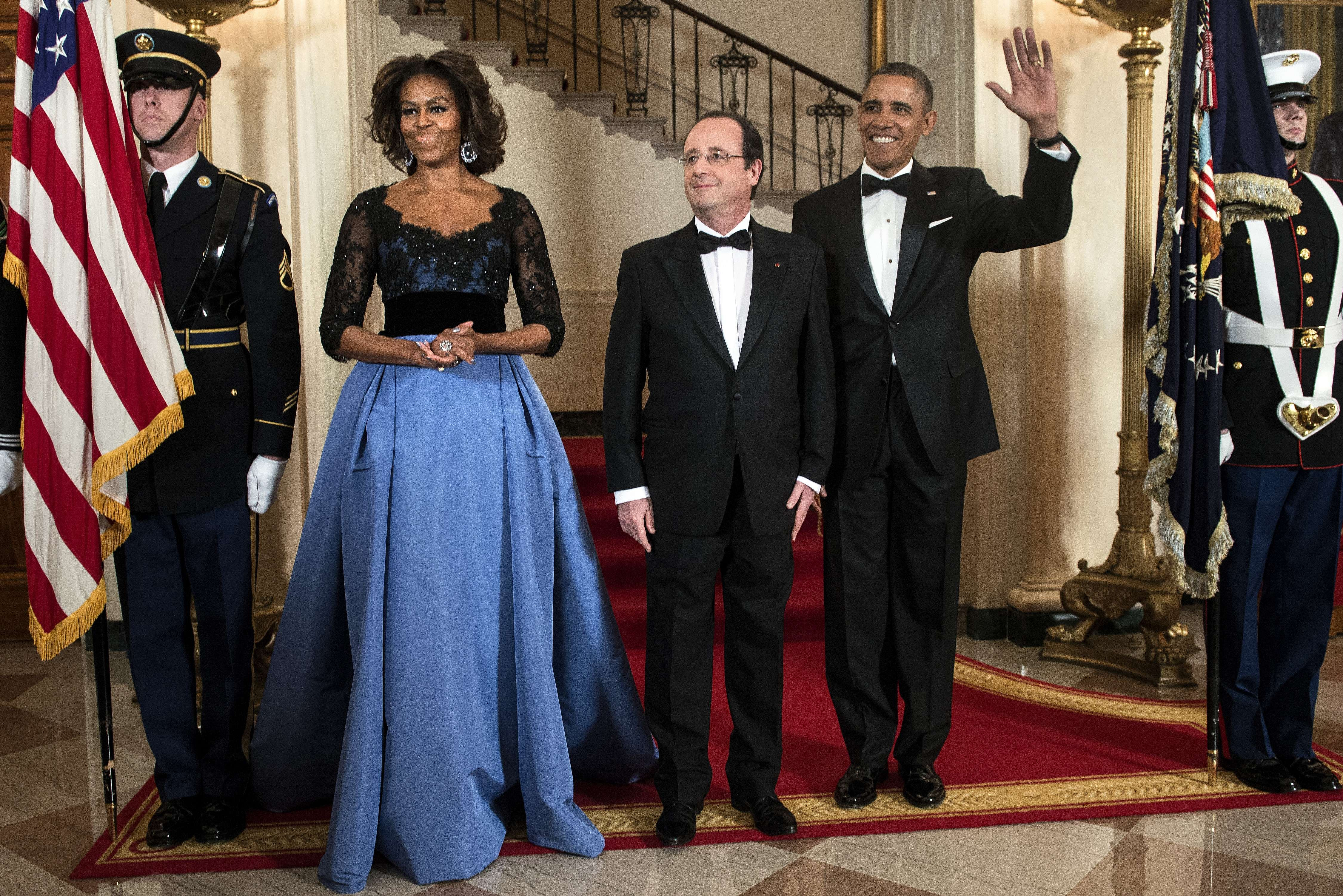 First Lady Michelle Obama, French President Francois Hollande and President Barack Obama pose in front of the Grand Staircase for an official photo before a State Dinner at the White House February 11, 2014 in Washington.