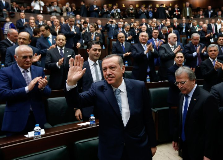 Turkey's Prime Minister Tayyip Erdogan greets his supporters as he arrives at a meeting at the Turkish parliament in Ankara