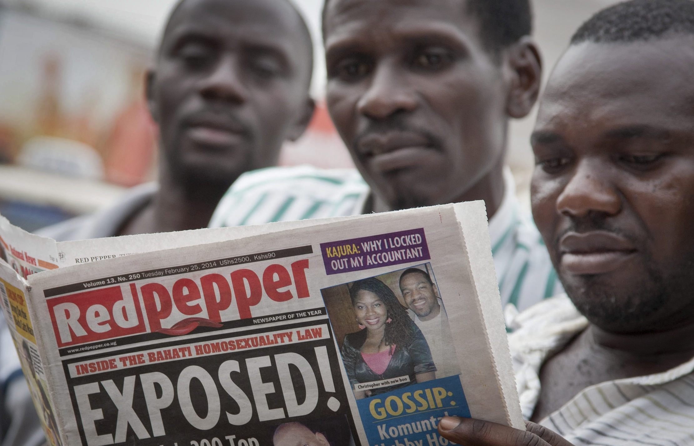 A Ugandan reads a copy of the  Red Pepper  tabloid newspaper in Kampala, Uganda Tuesday, Feb. 25, 2014.