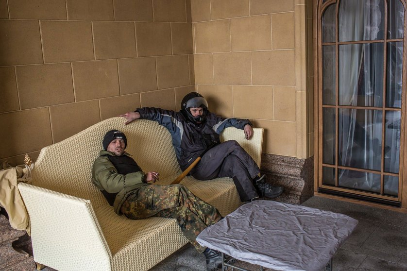 Anti-government protesters sit on a couch on a back patio.