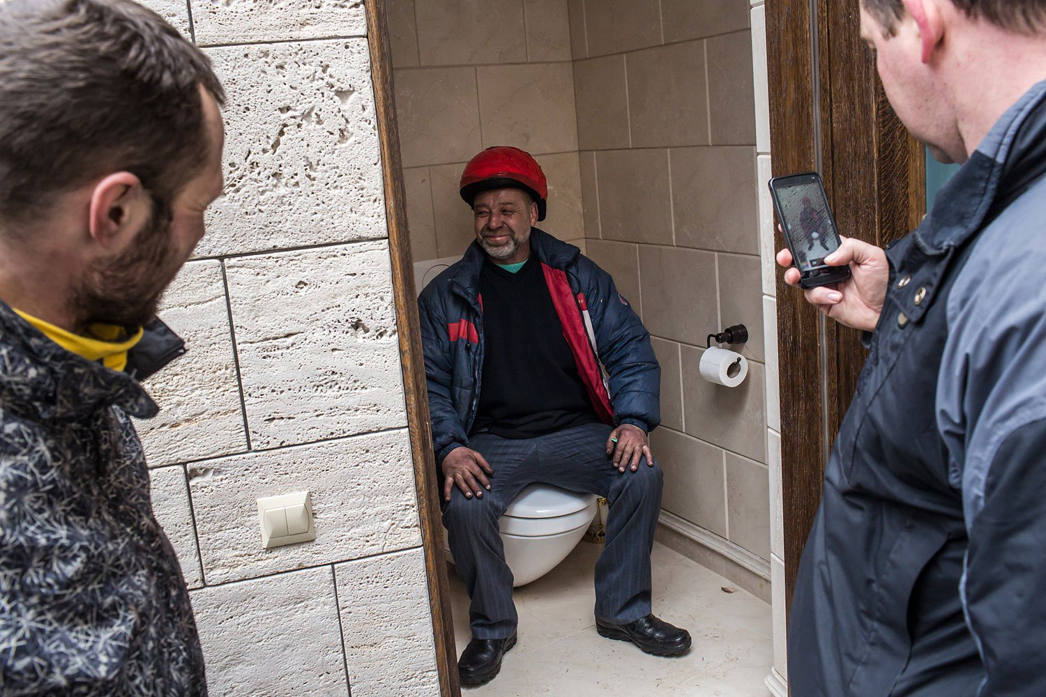 A man poses for a photo on a toilet.