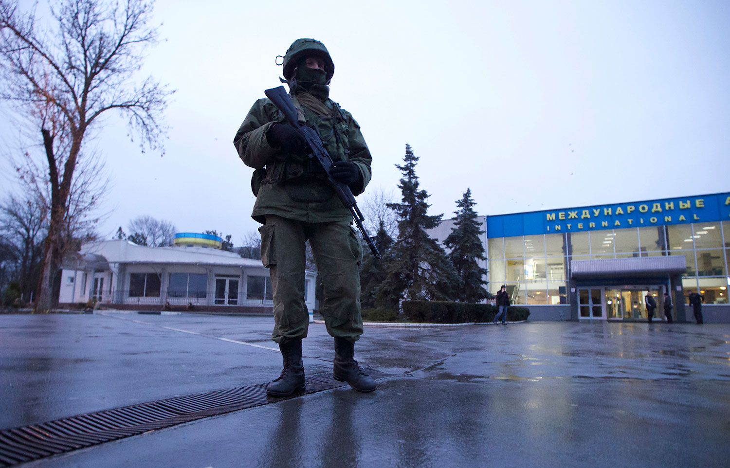 An unidentified armed man patrols a square in front of the airport in Simferopol, Ukraine, Feb. 28, 2014.