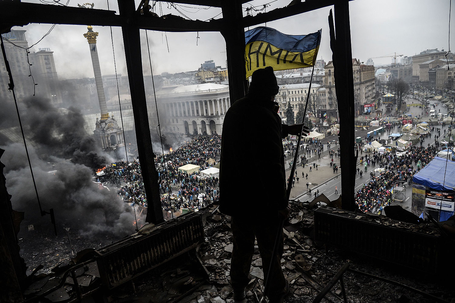 A demonstrator stands on a balcony overlooking Independence square in Kiev, Feb. 20, 2014