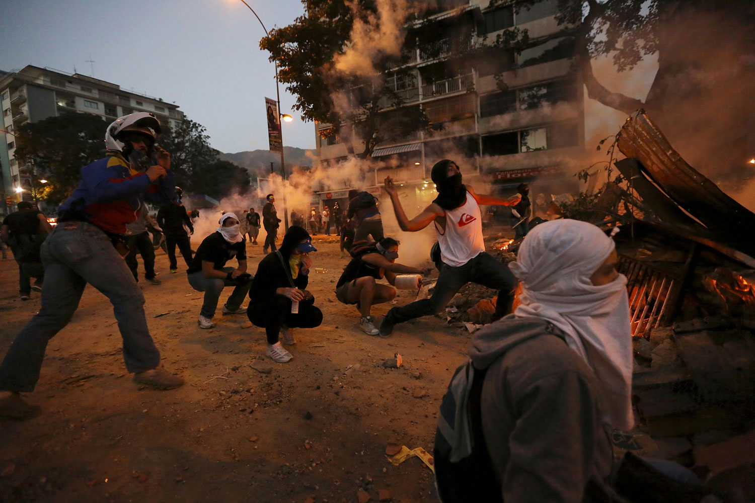 Masked demonstrators throw stones at Bolivarian National Police during clashes in Caracas, March 3, 2014.