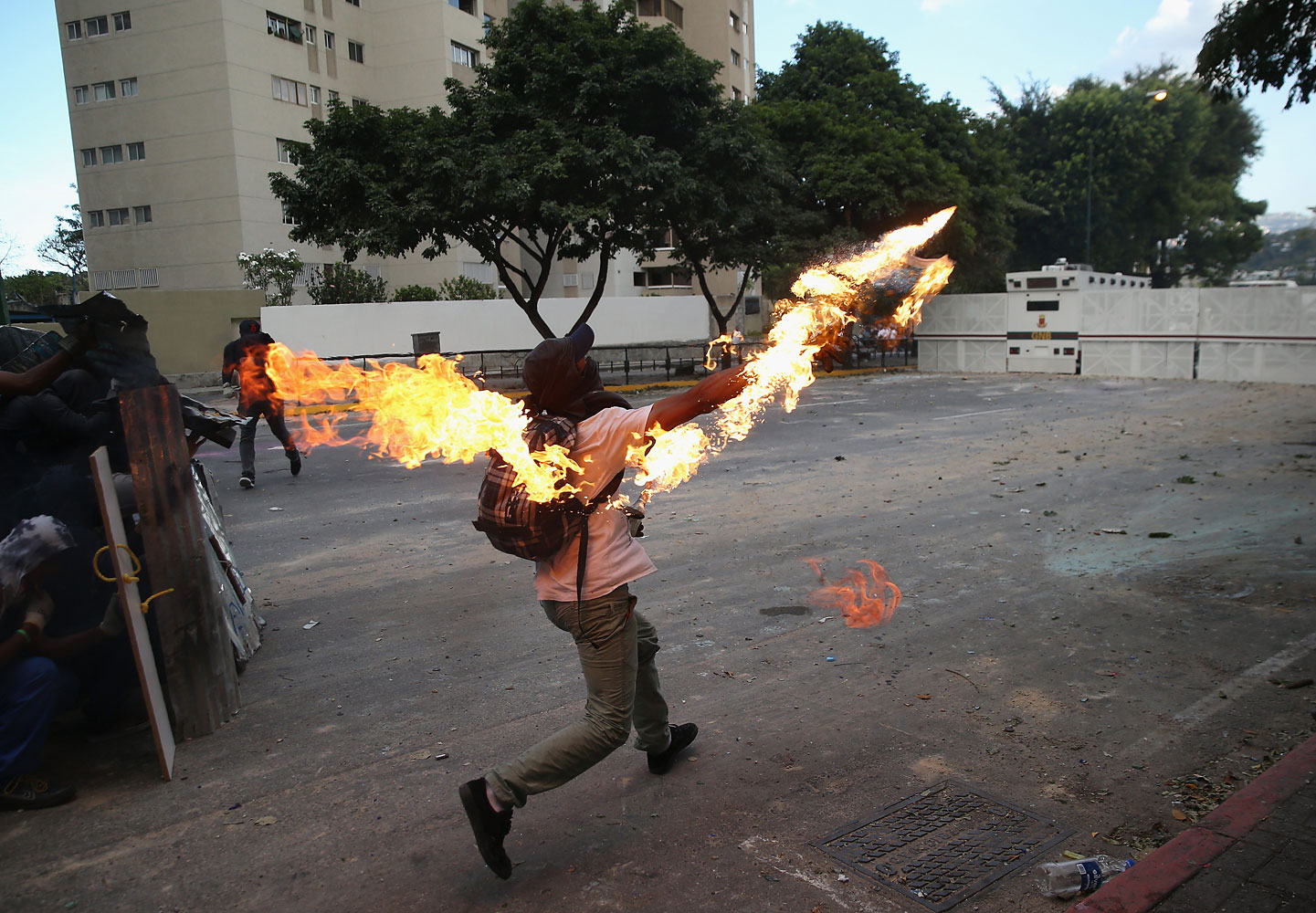 A protester hurls a molotov cocktail at National Guard troops in one of the largest anti-government demonstrations yet on March 2, 2014 in Caracas.