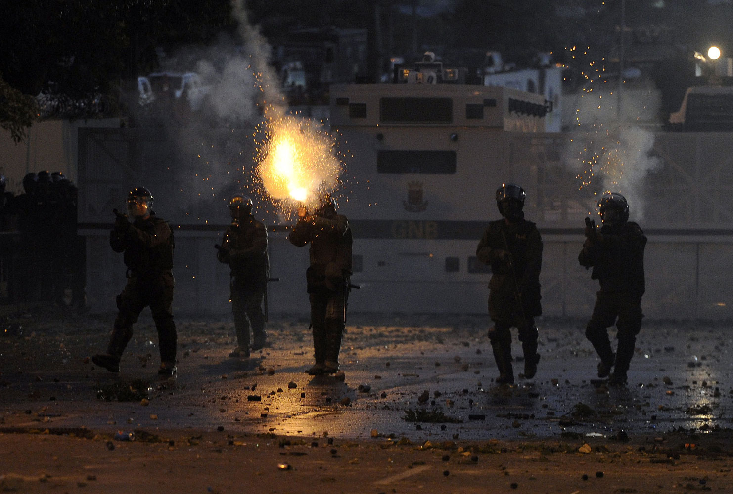 Members of the National Guard shoot during a protest against the government of Venezuelan President Nicolas Maduro, in Caracas on March 2, 2014.
