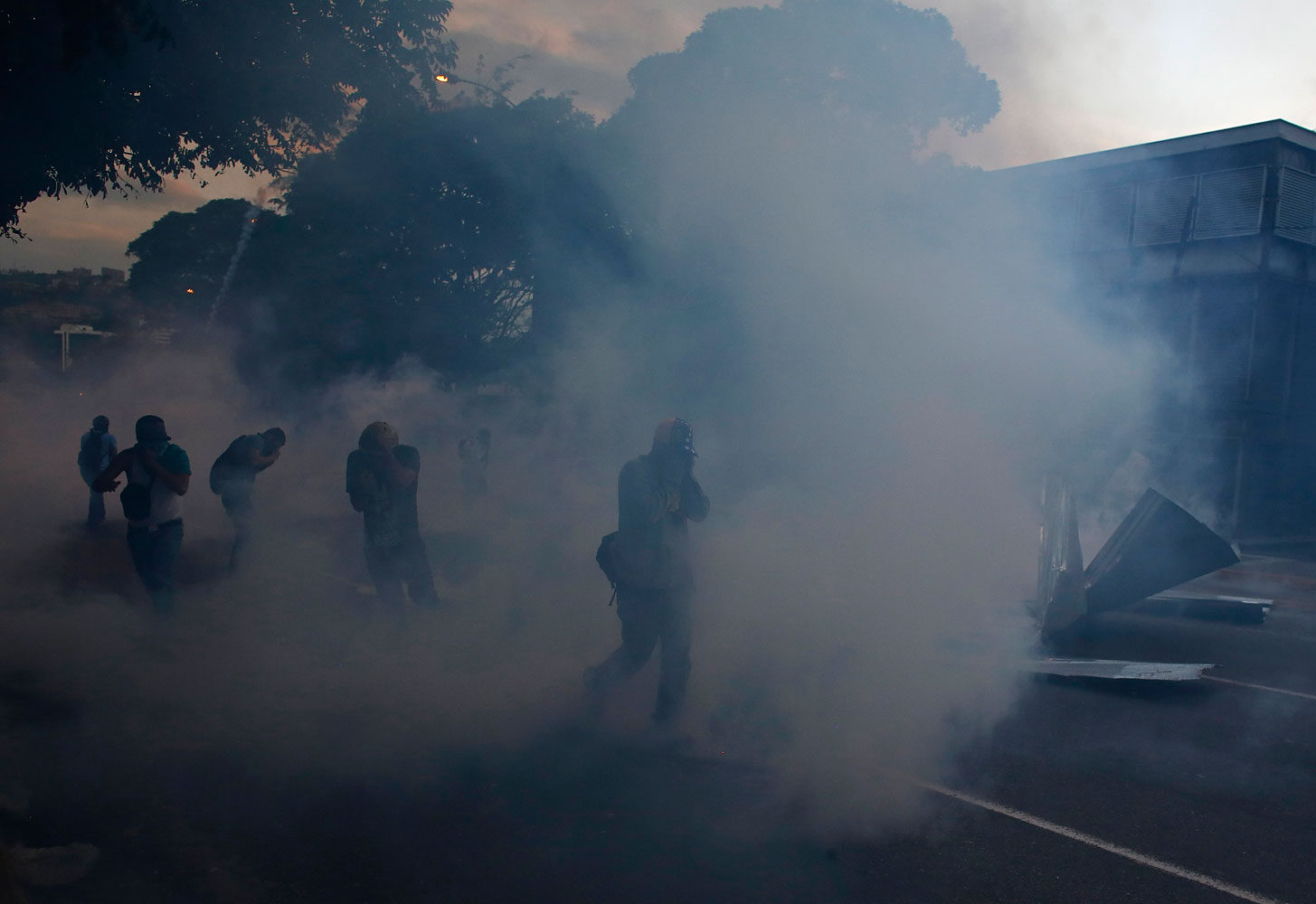 Anti-government protesters run away from tear gas during clashes with the national guard at Altamira square in Caracas, Feb. 28, 2014.