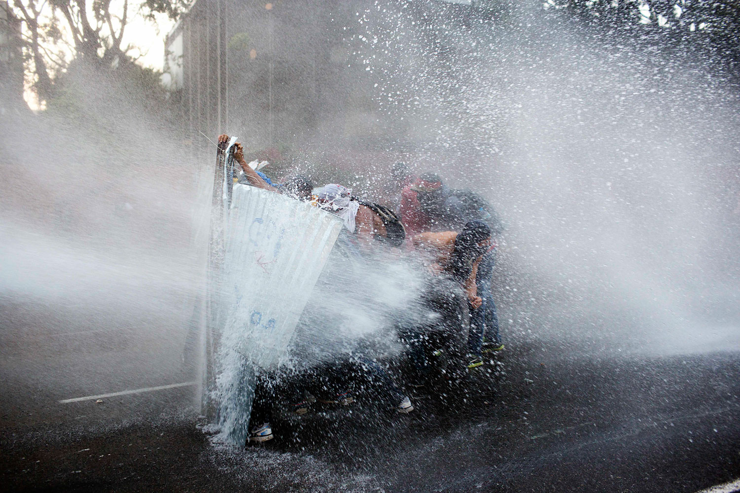 Anti-government demonstrators take cover from a police water cannon in Caracas, Feb. 28, 2014.