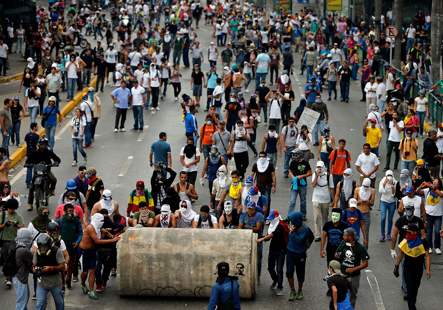 Demonstrators roll a water pipe in an attempt to block a major highway during clashes with the Bolivarian National Guard in Caracas, Feb. 27, 2014.