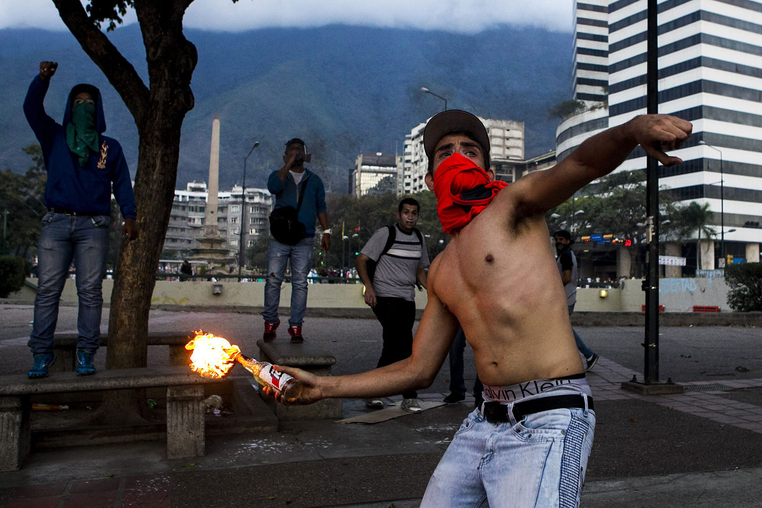 A demonstrator throws an incendiary device during clashes with Venezuelan National Bolivarian Guard during a protest against president Nicolas Maduro in Caracas, Venezuela, Feb. 27,  2014.