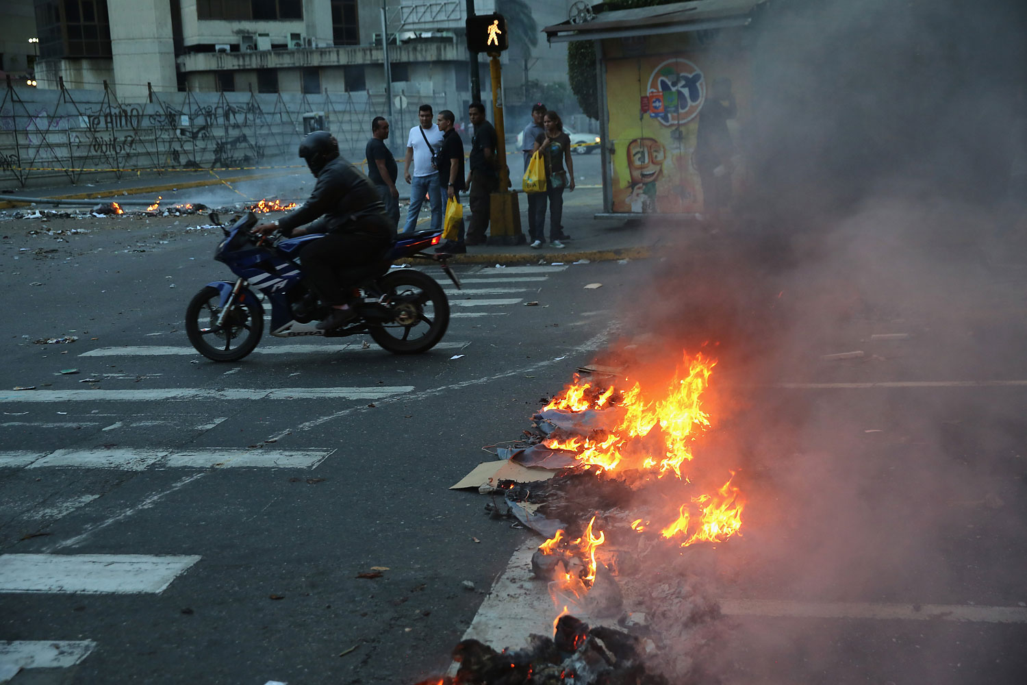 A motorcyclist rides through burning debris after an anti-government demonstration on Feb. 27, 2014 in Caracas.