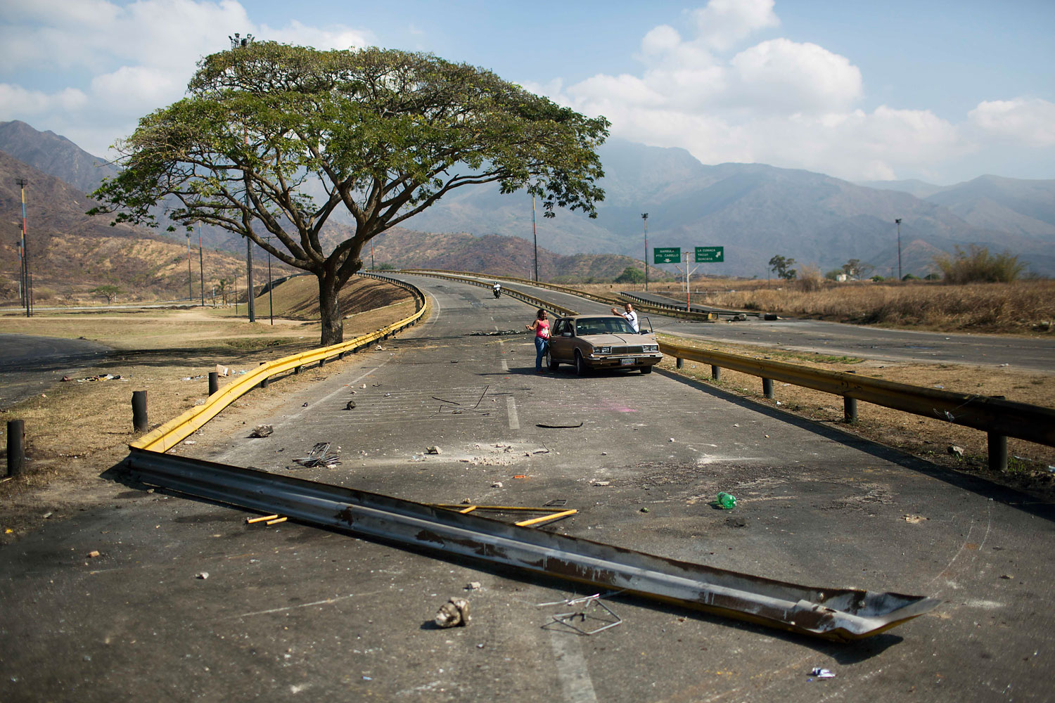 A couple stand next to their car trapped between barricades set up by anti-government protesters, in Valencia, Venezuela, Feb. 27, 2014.
