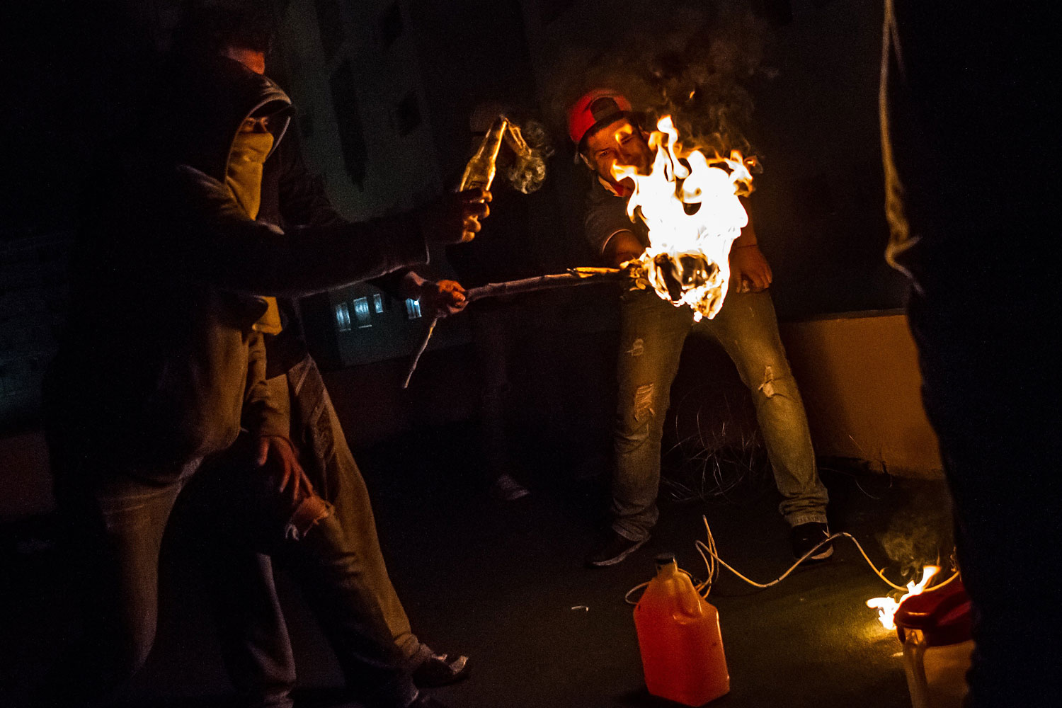 Protesters on a rooftop light Molotov cocktails to throw at police below in San Cristobal, Venezuela, in the pre-dawn hours of Feb. 24, 2014.