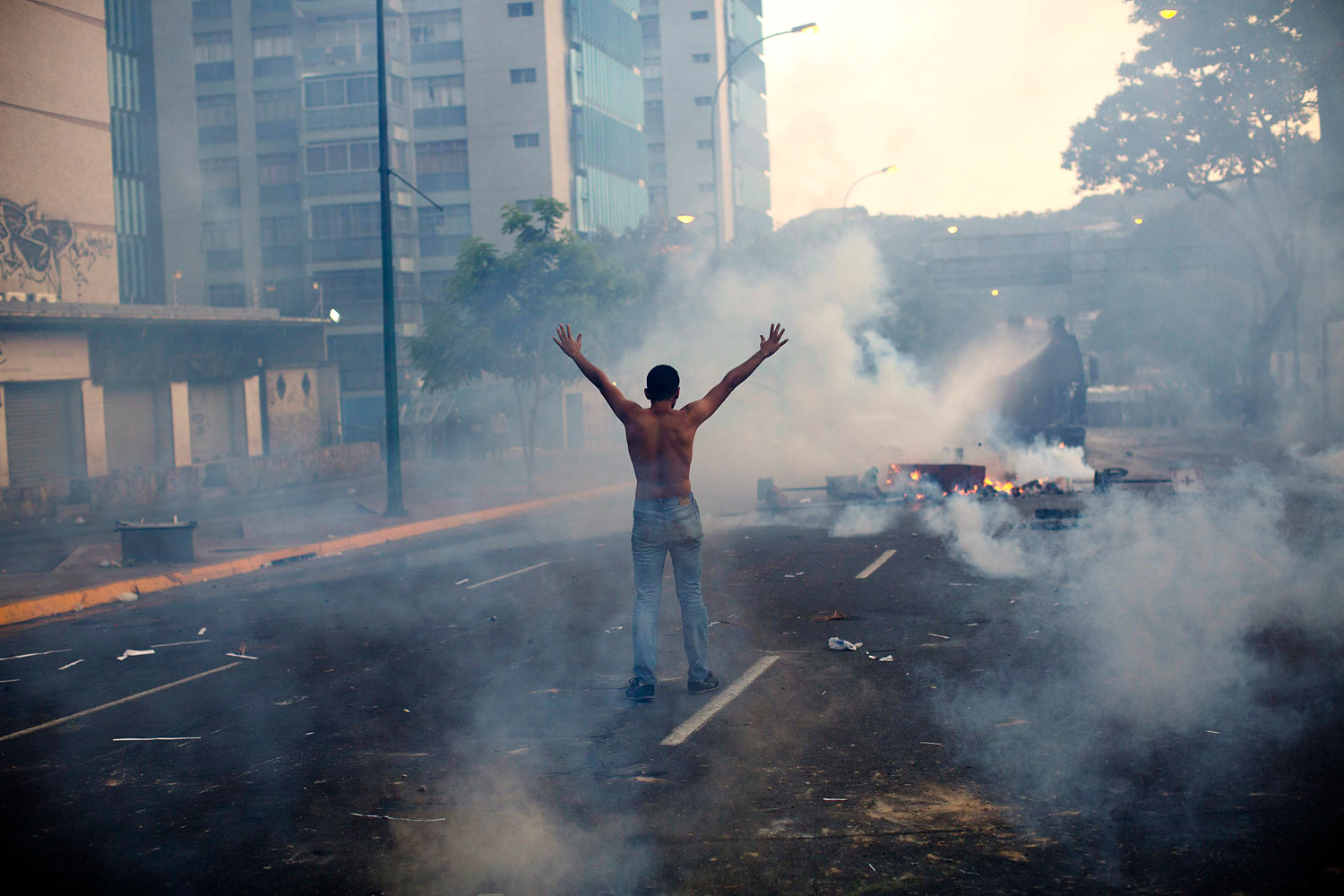 A demonstrator raises his arms toward the Bolivarian National Police firing tear gas and a water canon in the Altamira neighborhood of Caracas, Feb. 19, 2014.
