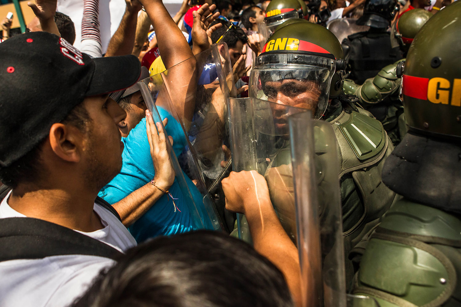 Lopez supporters clash with riot police in effort to block the path of the armored vehicle carrying Leopoldo Lopez after he surrendered to the police, in Caracas, Feb. 18, 2014.