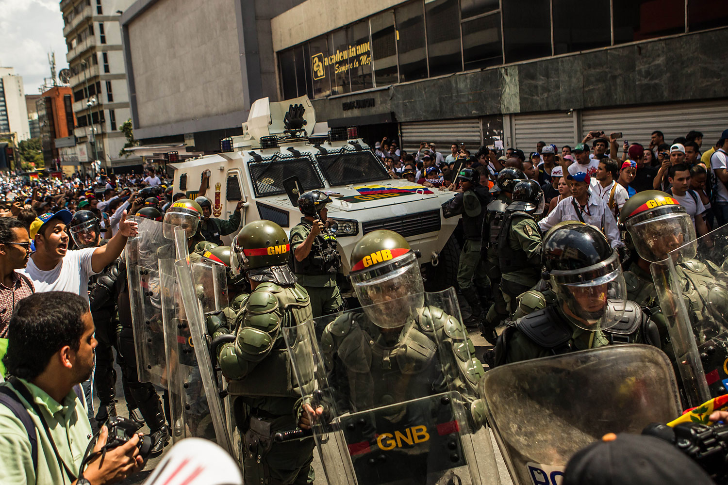 Riot police guard the armored vehicle with Leopoldo Lopez inside, in Caracas,  Feb. 18, 2014.