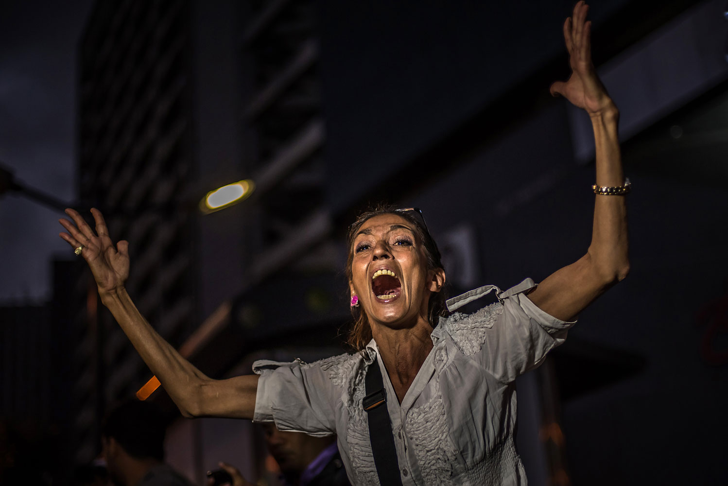 A mother yells at the riot police during a student protest against the Venezuelan government, in Caracas, Feb. 17, 2014.