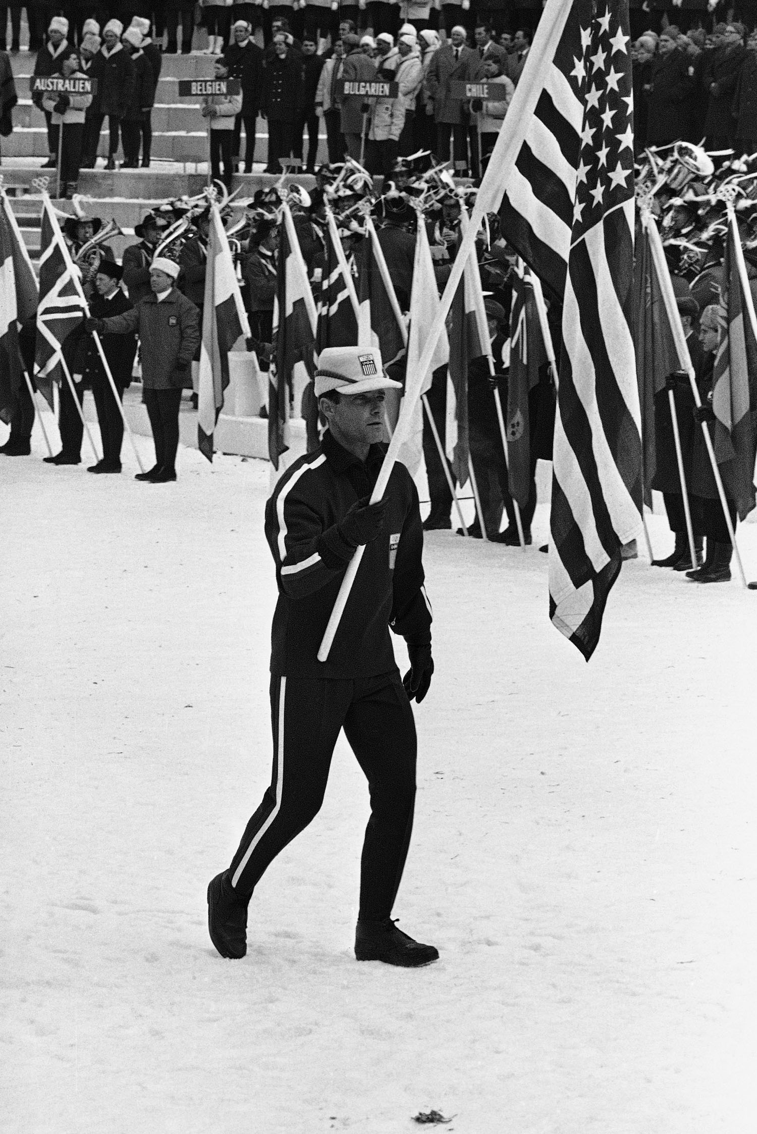 Speedskater Bill Disney carries the flag as he leads his team into the Olympic Ski Stadium at Bergisel for the opening ceremony of the 1964 Winter Olympics in Innsbruck, Austria.