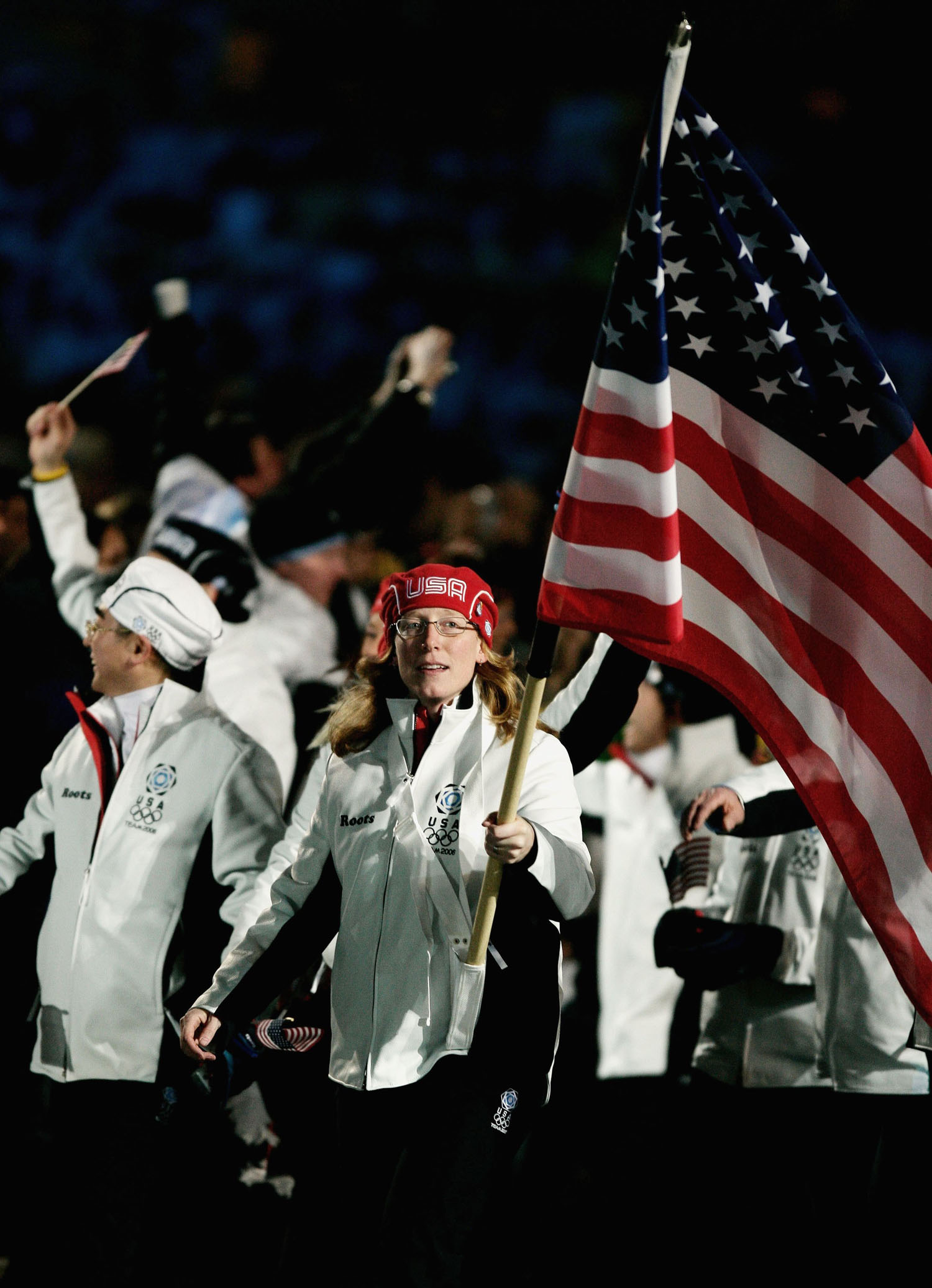 Speed skater Chris Witty carries the US flag as she and her teammates attend the opening ceremony of the Turin Winter Olympic Games on Feb. 10, 2006.