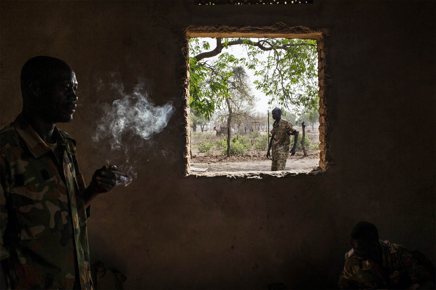 Feb. 15, 2014. A Sudan People's Liberation Army (SPLA) government soldier from the 2nd Battalion smokes a cigarette at the SPLA headquarters in Nyang, in the county of Yirol East, South Sudan.