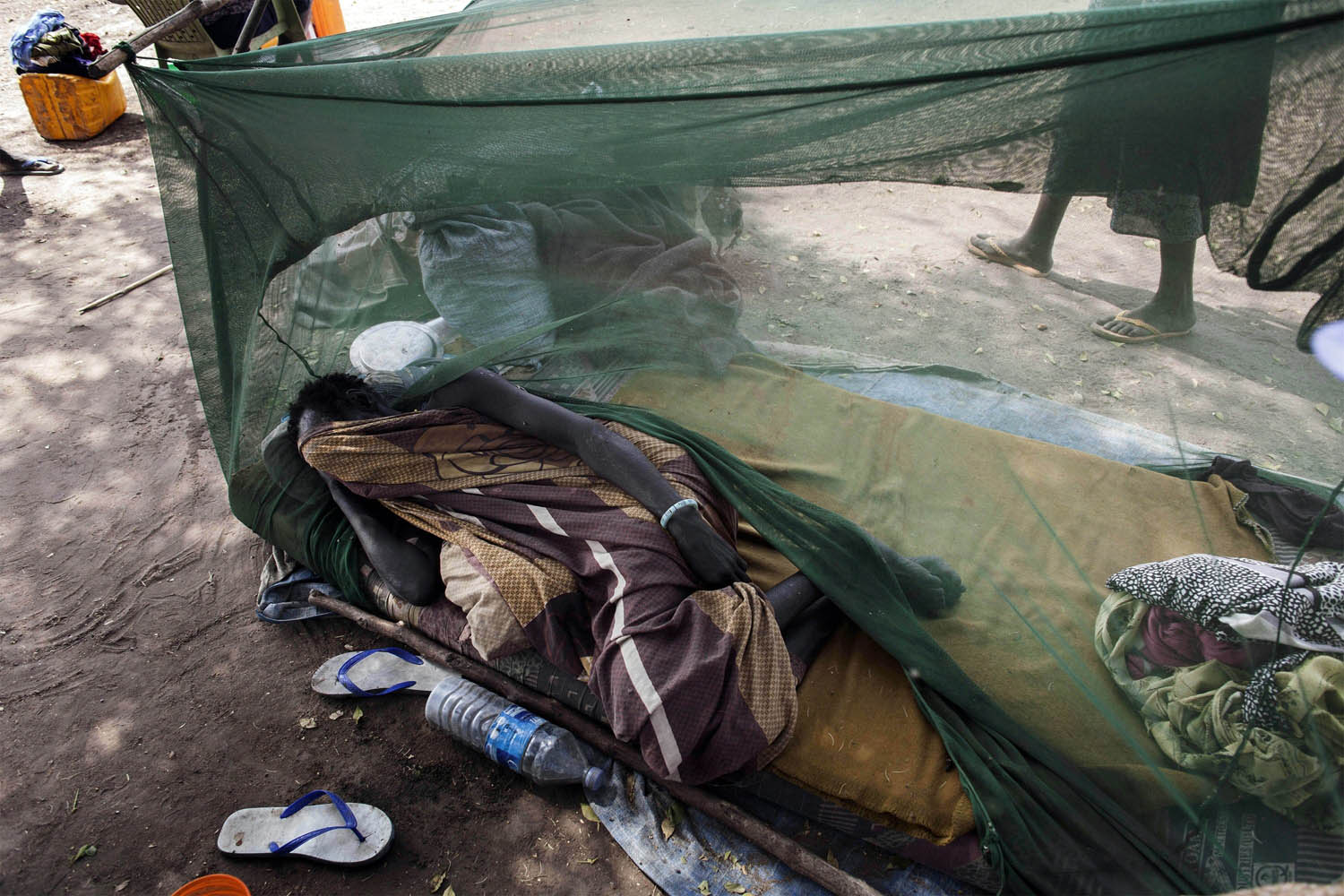 Feb. 5, 2014. A South Sudanese woman lies under a mosquito net in a temporary camp for internally displaced persons in Mingkaman, South Sudan,