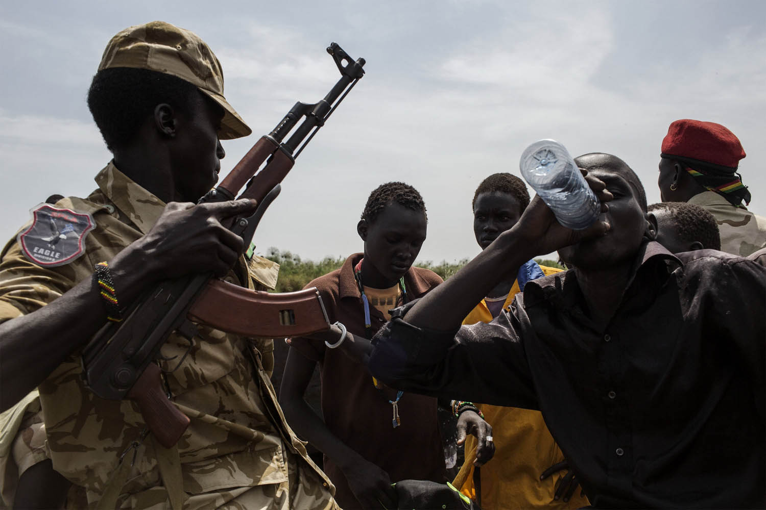 Feb. 9, 2014. Soldiers stand next to South Sudanese internally displaced people (IDP) waiting on a boat at Mingkaman's temporary camp,  as they head back to Bor, South Sudan..