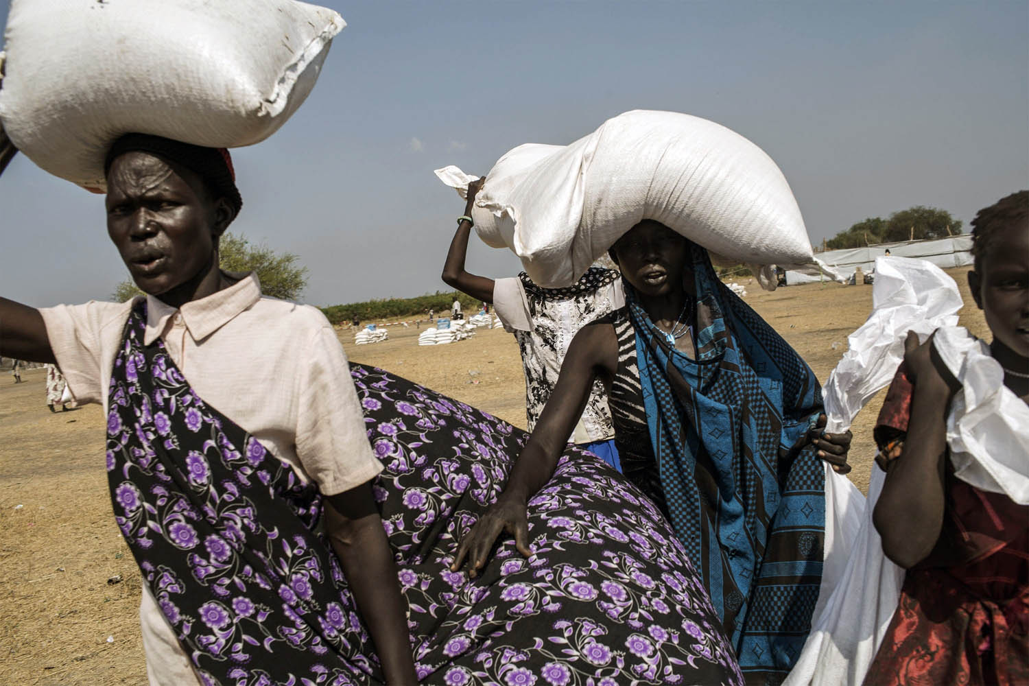 Feb. 9, 2014. South Sudanese internally displaced people (IDP) carry food supplies, distributed by the International Committee of the Red Cross (ICRC) at the Mingkaman temporary camp, South Sudan.