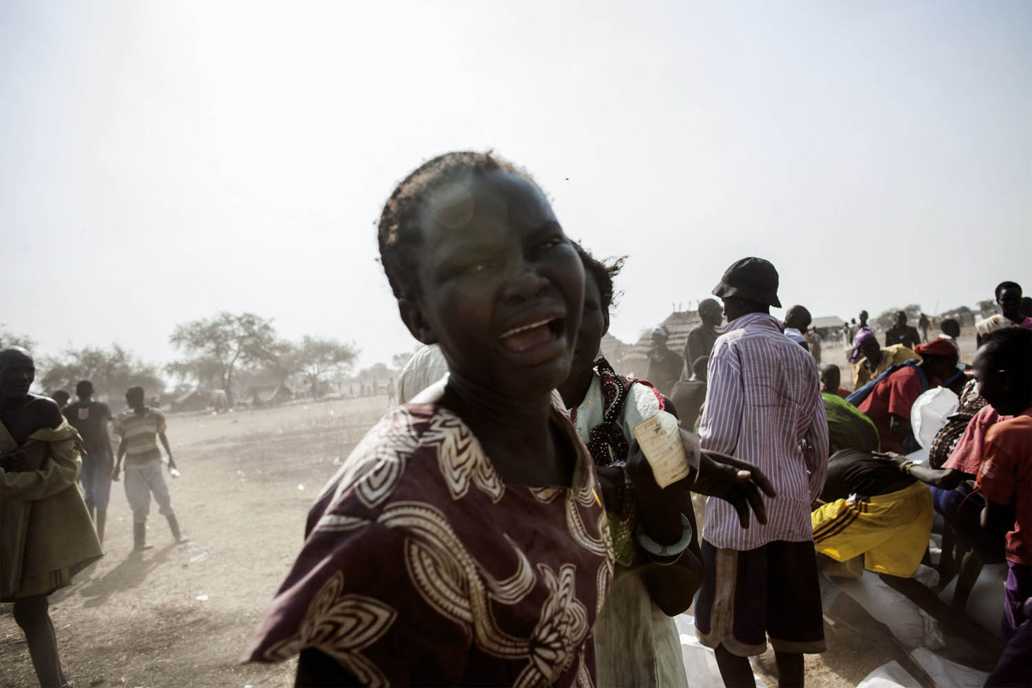 Feb. 9, 2014. A South Sudanese woman reacts as South Sudanese internally displaced people (IDP) fight for food supplies, distributed by the International Committee of the Red Cross (ICRC) at the Mingkaman temporary camp, South Sudan.